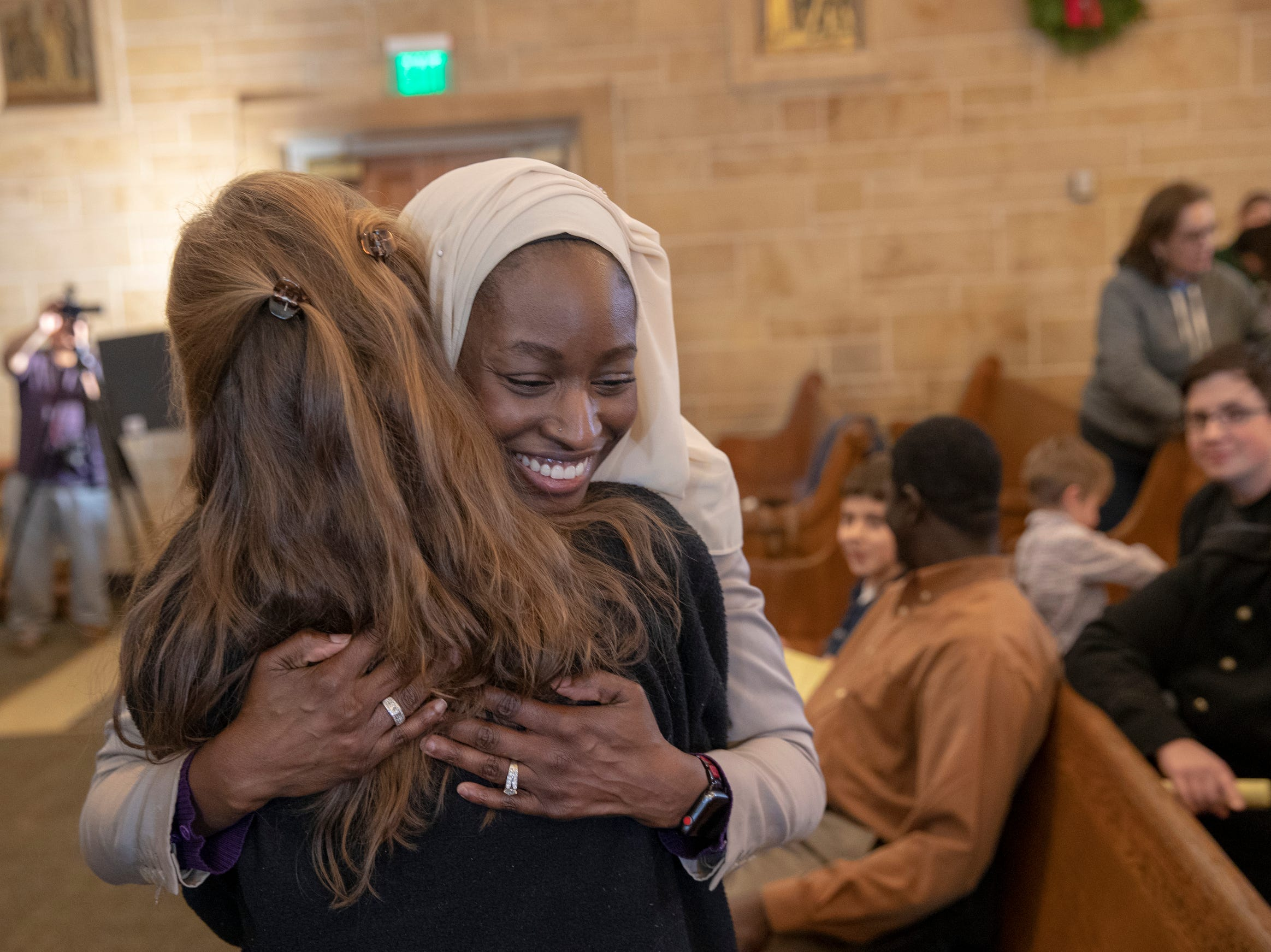 Halima Al-Khattab (left), gives a hug to Carol Tharp-Perrin, during a Christian-Muslim prayer service at Saint Philip Neri Catholic Church, Indianapolis, Sunday, Dec. 16, 2018.