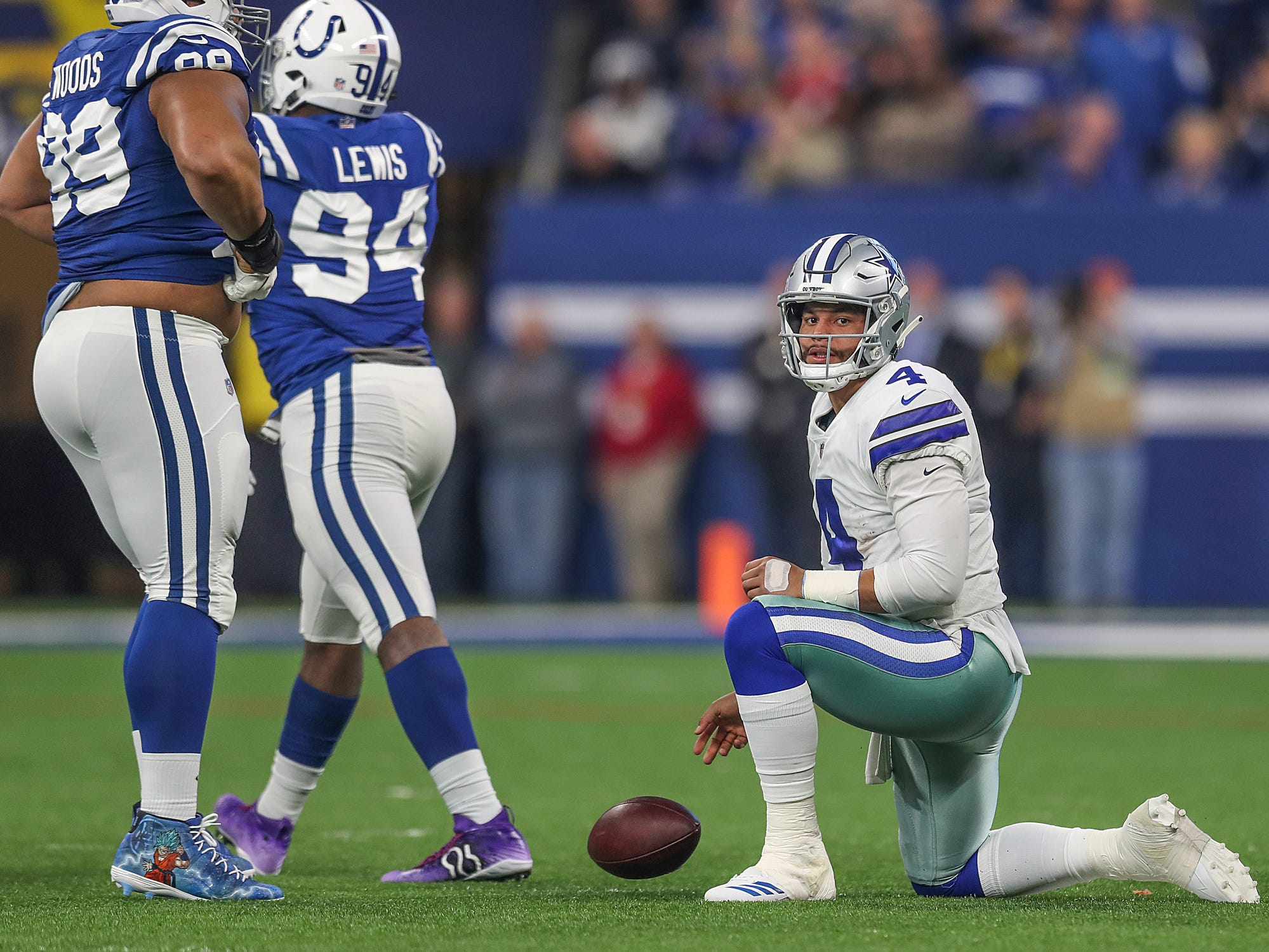 Dallas Cowboys quarterback Dak Prescott (4) gets up slowly while Indianapolis Colts Al Woods (99) and Tyquan Lewis (94) celebrate Lewis' sack in the first half of the game at Lucas Oil Stadium in Indianapolis, Sunday, Dec. 16, 2018.