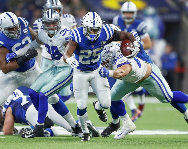 Indianapolis Colts running back Marlon Mack (25) runs through the Dallas Cowboys defense in the second half of their game at Lucas Oil Stadium on Sunday, Dec. 16, 2018. The Colts shut-out the Cowboys 23-0.