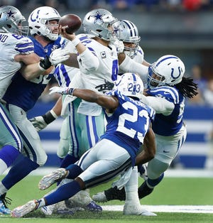 Dallas Cowboys quarterback Dak Prescott (4) is pressured by Indianapolis Colts cornerback Kenny Moore (23), Denico Autry (96) and Margus Hunt (92) in the second half of their game at Lucas Oil Stadium on Sunday, Dec. 16, 2018. The Colts shut-out the Cowboys 23-0.