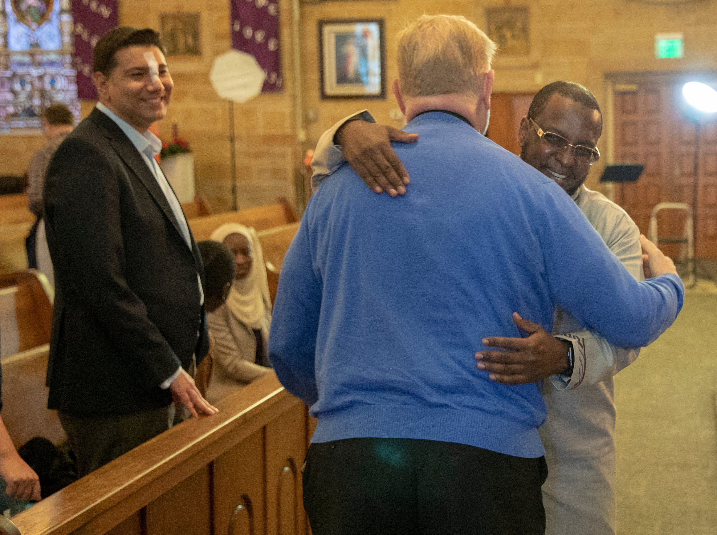 Eyas Raddad (left), watches as fellow Muslim Imam Ahmed Al-Amine (right), embraces Fr. Rick Ginther, a member of Our Lady of Lourdes, before a Christian-Muslim prayer service at Saint Philip Neri Catholic Church, Indianapolis, Sunday, Dec. 16, 2018. The service is the second annual, and joins people from this church and Indianapolis' Masjid Al-Fajr.