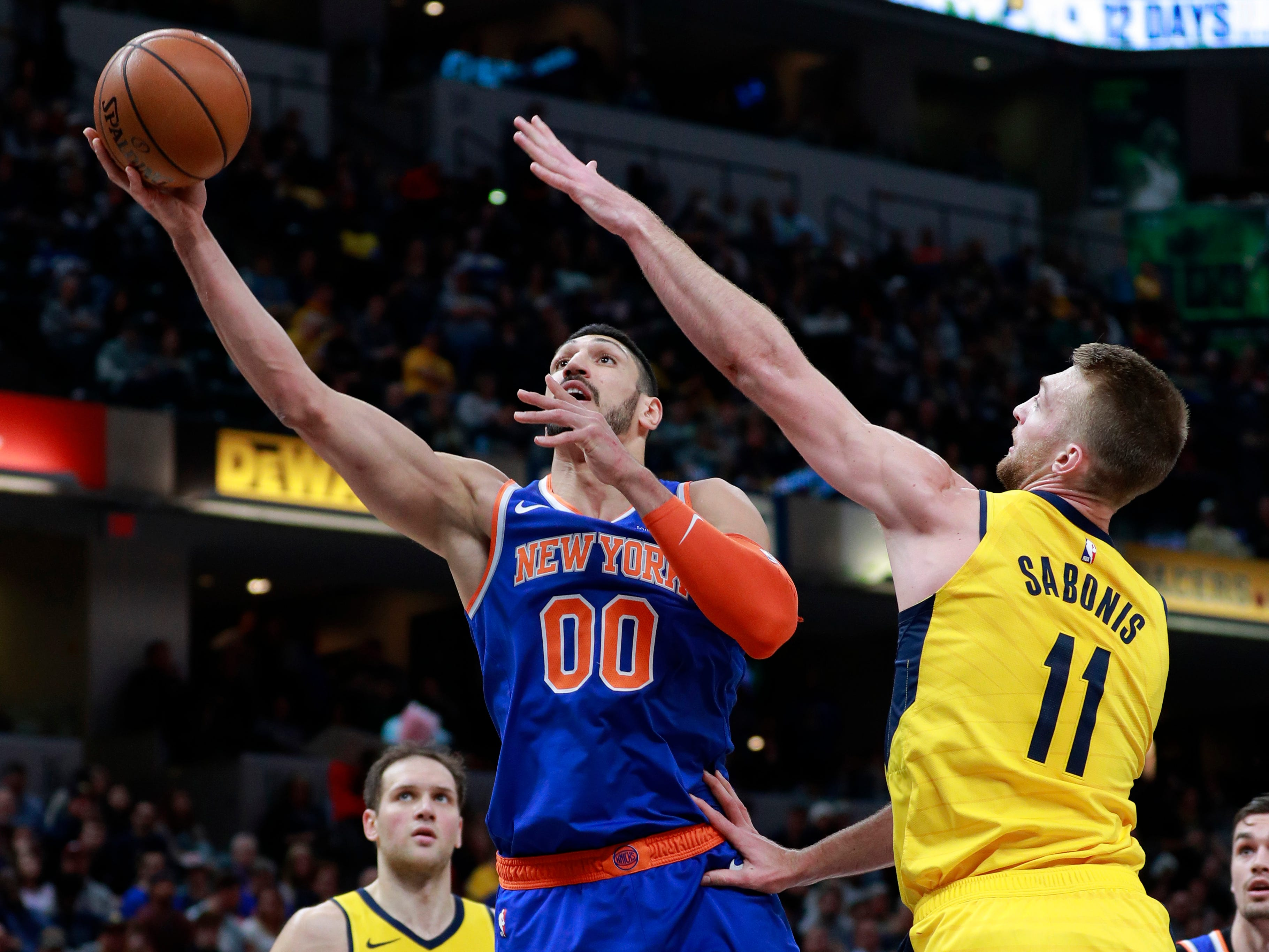 New York Knicks center Enes Kanter (00) shoots the basketball defended by Indiana Pacers forward Domantas Sabonis during the first half of an NBA basketball game, Sunday, Dec. 16, 2018, in Indianapolis.