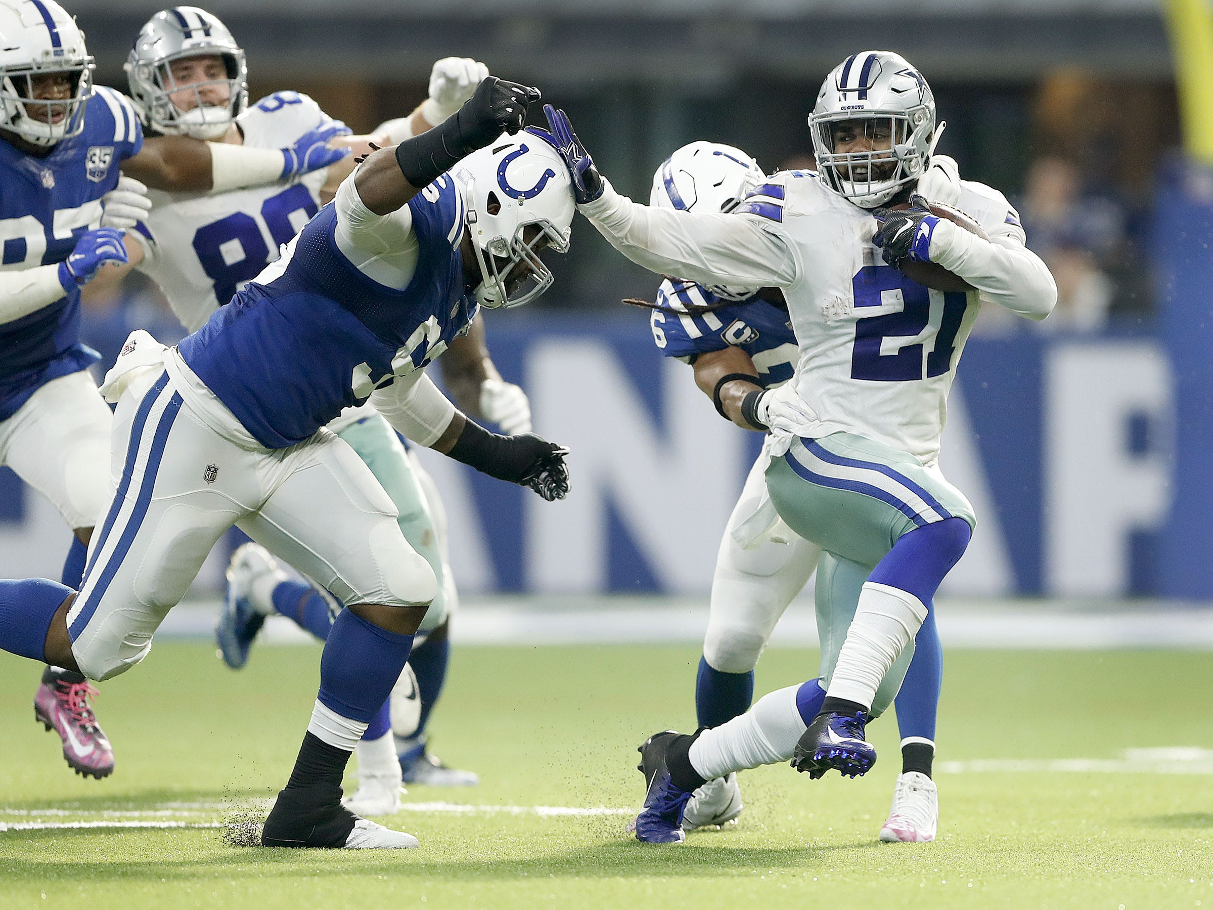 Indianapolis Colts defensive tackle Denico Autry (96) reaches out to tackle Dallas Cowboys running back Ezekiel Elliott (21 in the first half of their game at Lucas Oil Stadium on Sunday, Dec. 16, 2018.