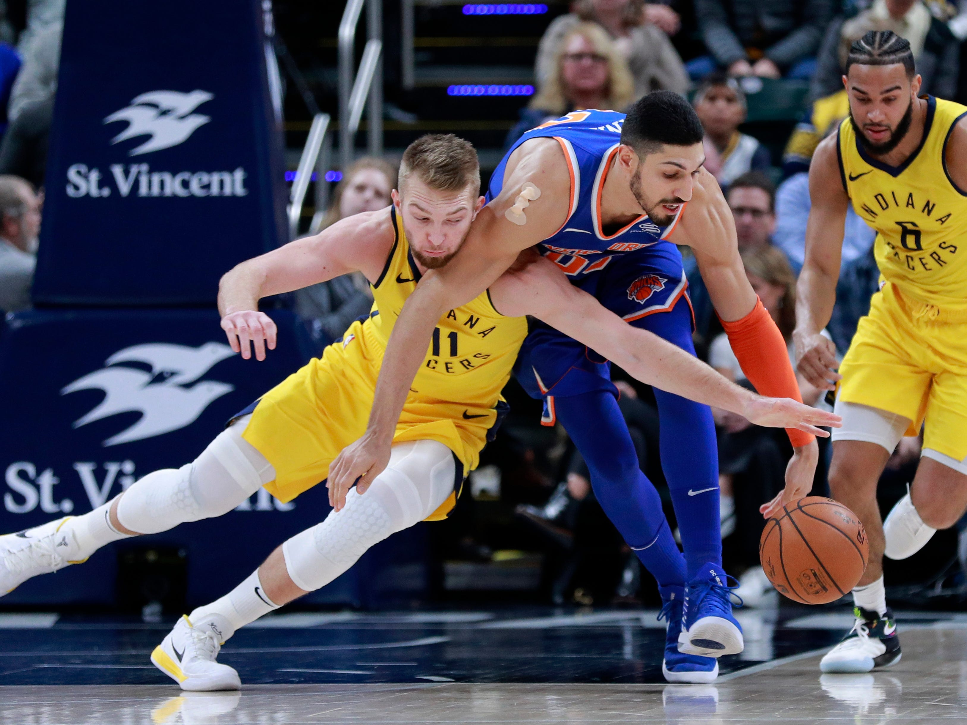 Indiana Pacers forward Domantas Sabonis, left, and New York Knicks center Enes Kanter fight for the basketball near Pacers guard Cory Joseph, right, during the first half of an NBA basketball game, Sunday, Dec. 16, 2018, in Indianapolis. (AP Photo/R Brent Smith)