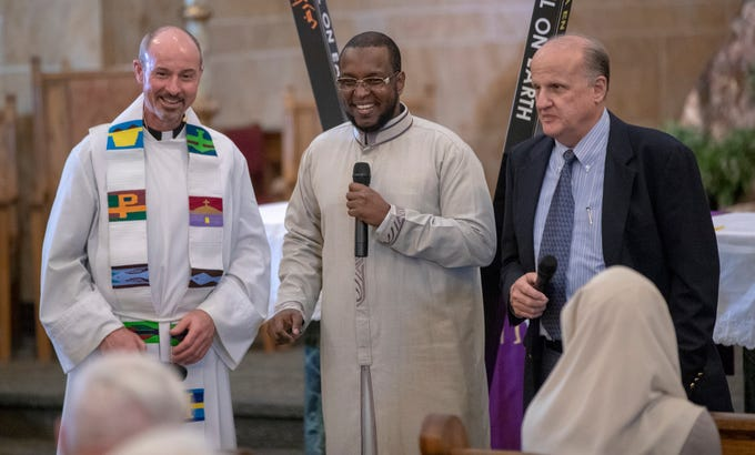 Fr. Chris Wadelton (left), Imam Ahmed Al-Amine, and moderator T. A. Shula, smile near the end of a Christian-Muslim prayer service at Saint Philip Neri Catholic Church, Indianapolis, Sunday, Dec. 16, 2018. The service is the second annual, and joins people from this church and Indianapolis' Masjid Al-Fajr.
