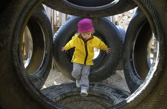 On a sunny Sunday afternoon a curiousity driven three-year-old Amy Maxwell explores into an enclosure of tires at the Fort Kid playground.