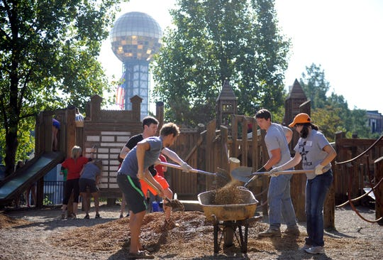 Volunteers Matthew Morton, Adam Thomas, Jim Gall, and Molly McCoy, from left, shovel gravel into a wheelbarrow while working on renovations at the Fort Kid Playground in Knoxville on Saturday, Sept. 20, 2014.