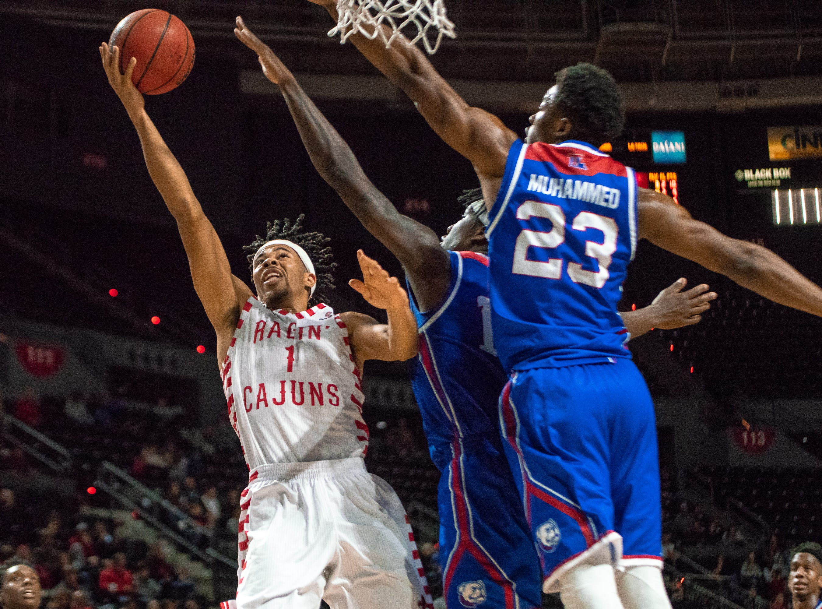 UL's Malik Marquetti attempts to score a layup against the opposing guards as the Ragin' Cajuns take on the LA Tech Bulldogs at the Cajundome on December 15, 2018.
