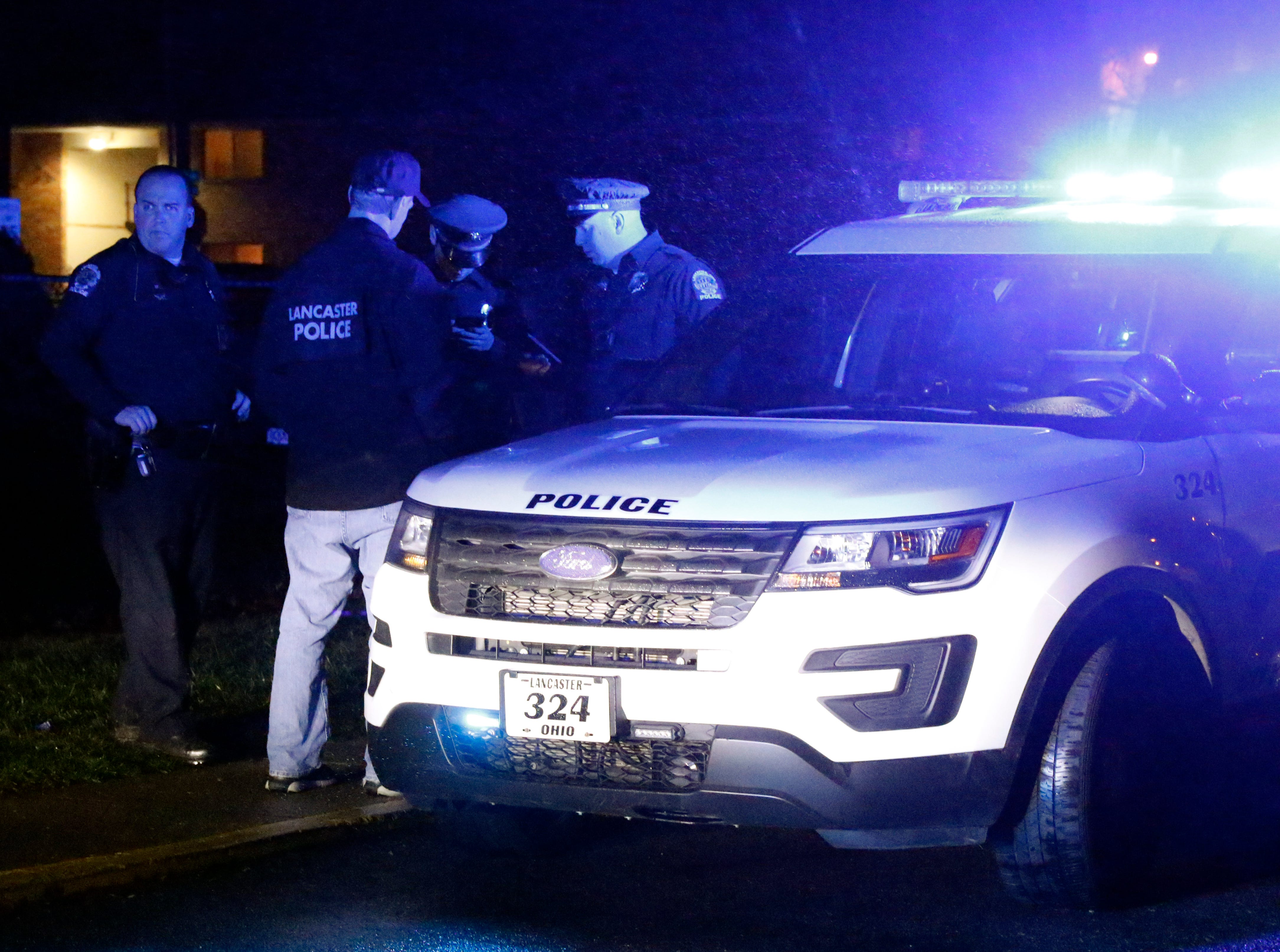 Lancaster Police Officers talk at the Lancaster Club Apartments on Sells Road Saturday night, Dec. 15, 2018, in Lancaster. Officers responded to a shooting that sent two people to the hospital.