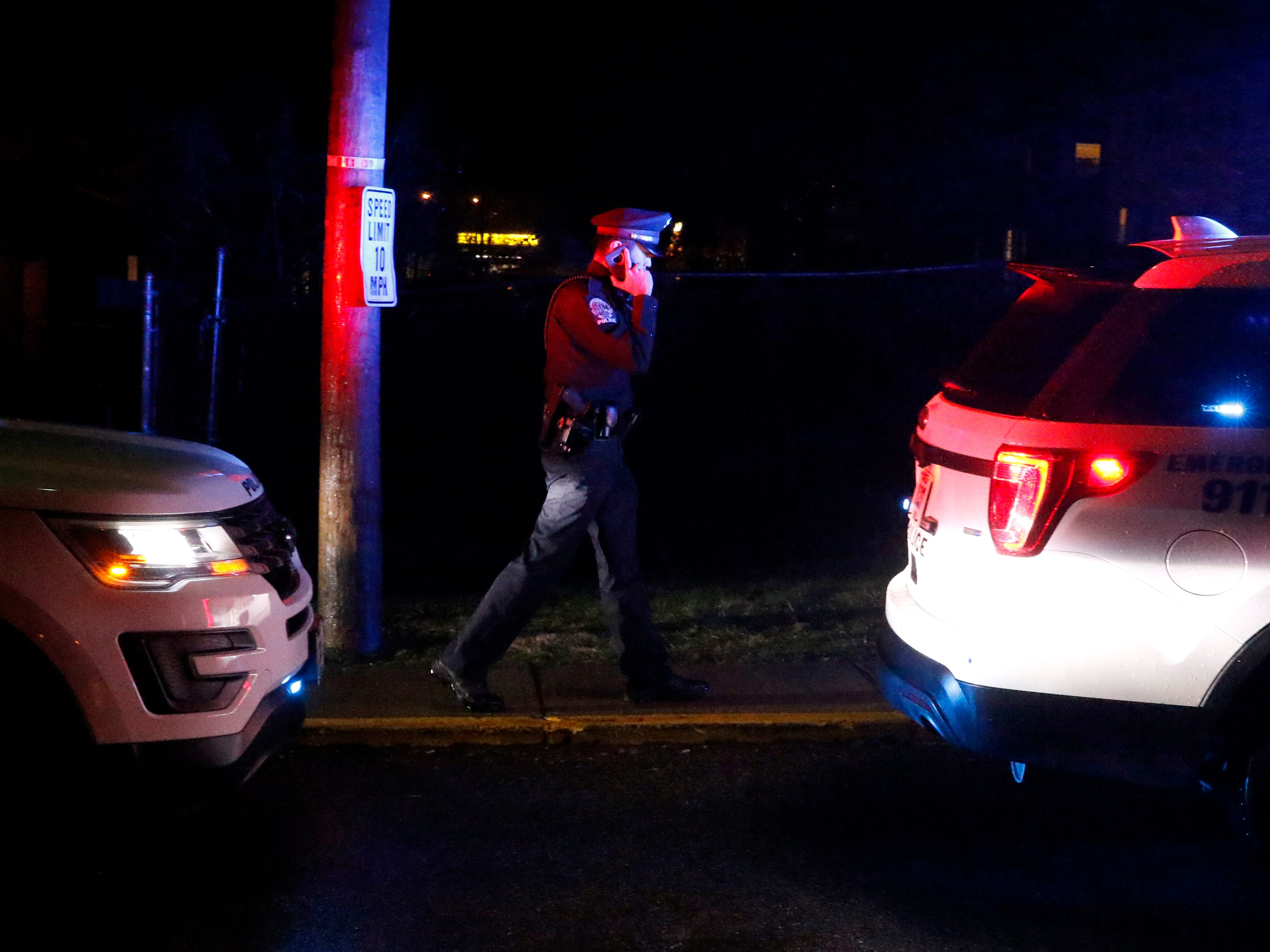 A Lancaster Police Officer walks between cruisers as he speaks on the phone Saturday night, Dec. 15, 2018, in Lancaster. Officers responded to a shooting a Lancaster Club Apartments that sent two people to the hospital.