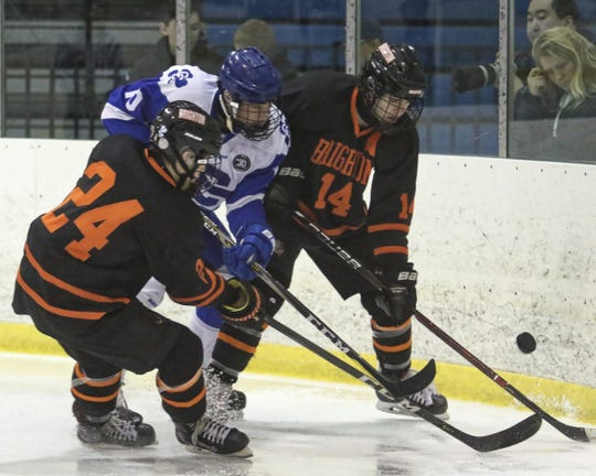 Jason Verhelle (14) and Michael Forfinski (24) of Brighton battle Detroit Catholic Central's Eli Brown for the puck on Saturday, Dec. 15, 2018.