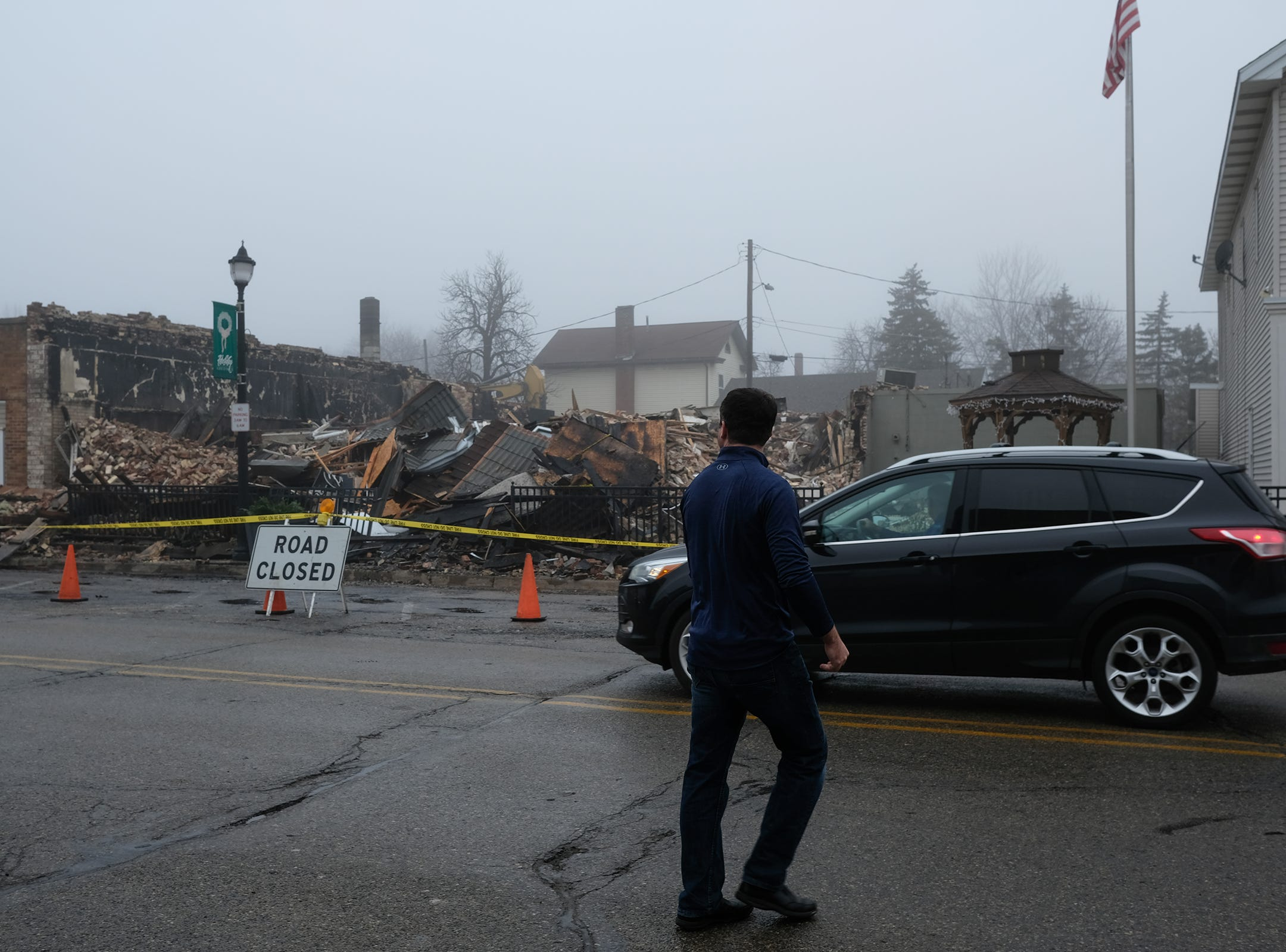 Motorists and pedestrians look at the destruction caused by a fire in downtown Fowler on Saturday. Photo: Sunday, Dec. 16, 2018.
