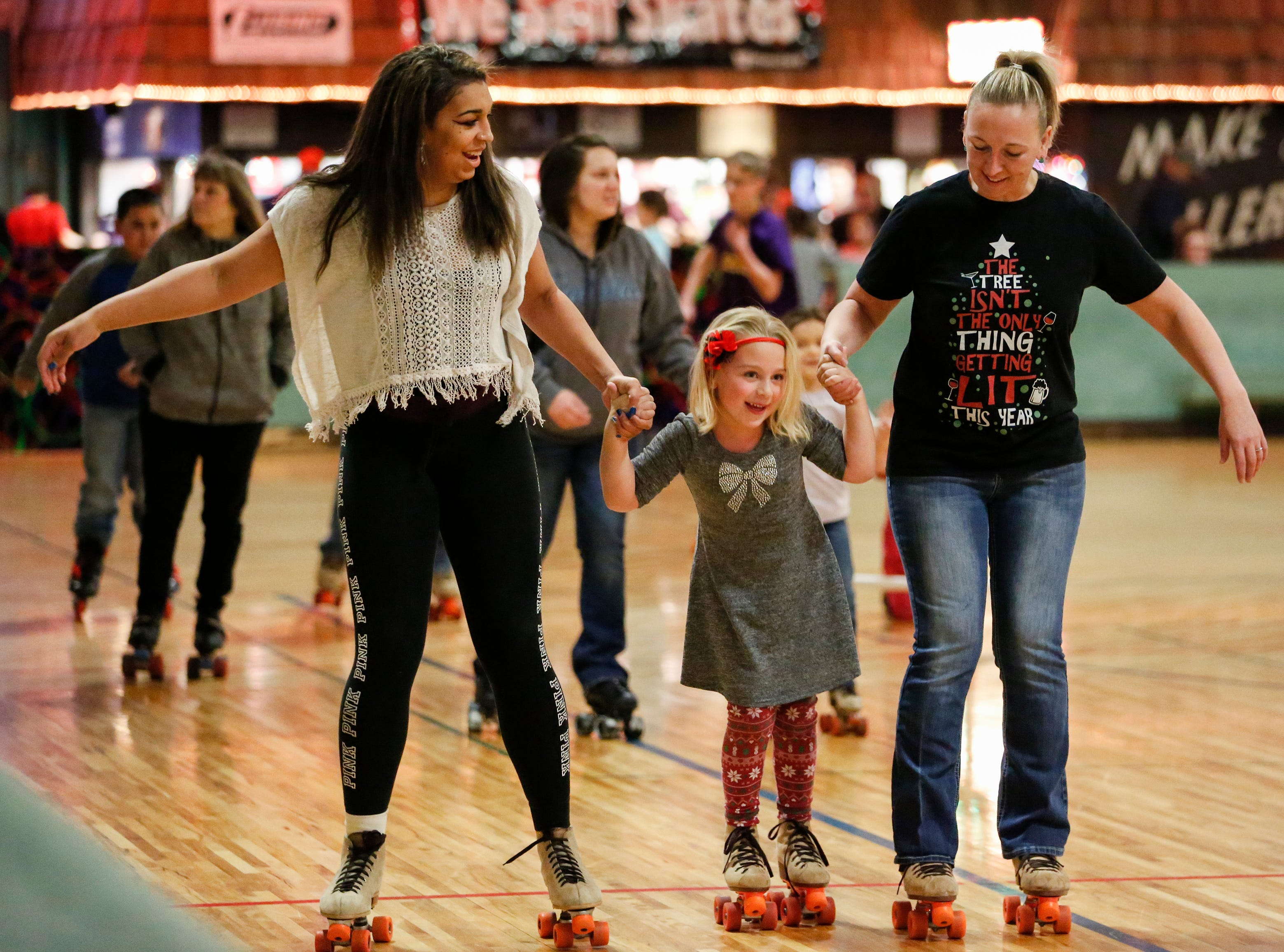 Valentina Stueck, 15, and Bailey Peters, 6, skate with their mom Amy Peters during the 20th annual Santa Skate at Rollaire Skate Center Saturday, December 15, 2018, in Manitowoc, Wis. Joshua Clark/USA TODAY NETWORK-Wisconsin