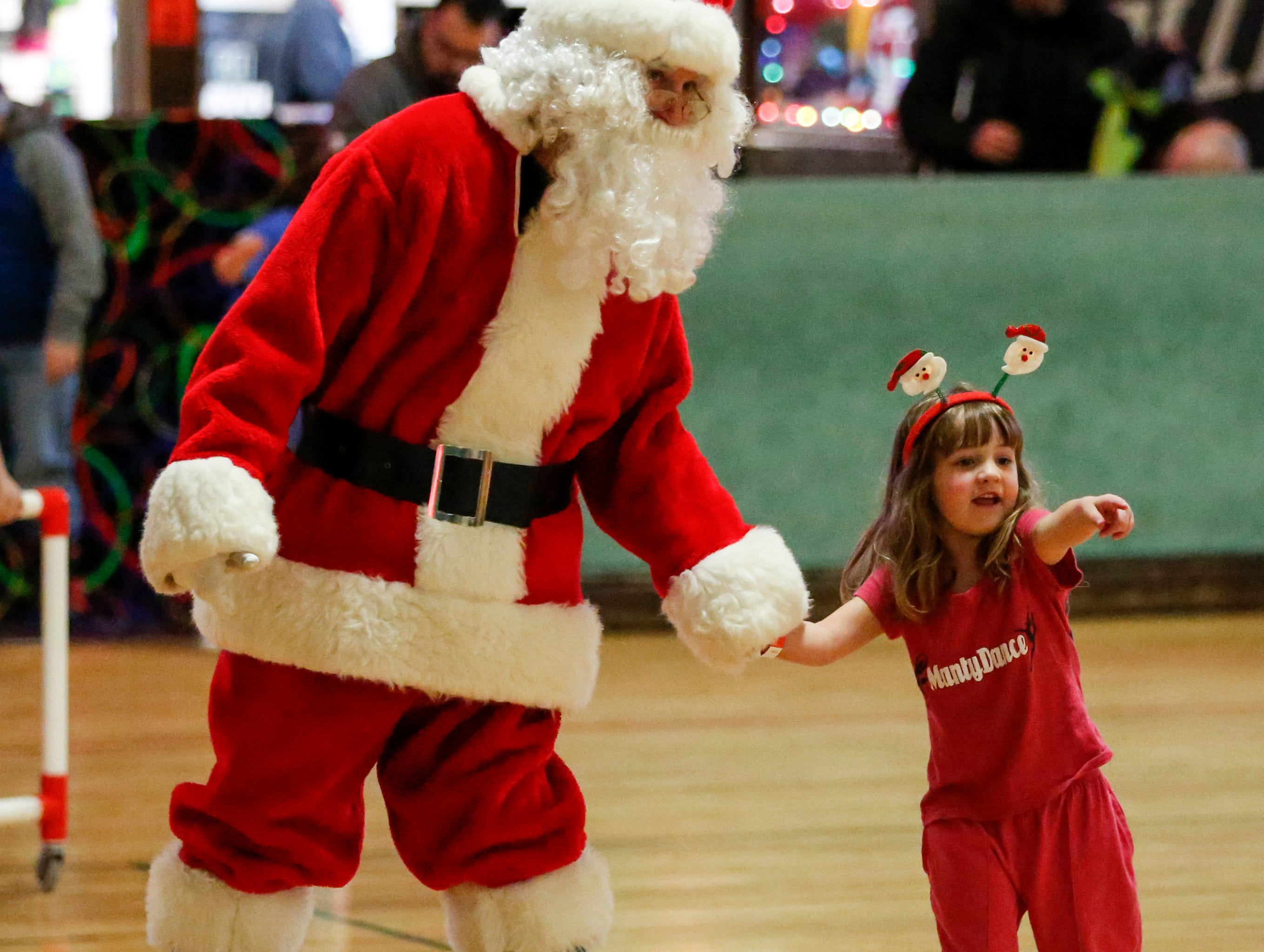 Santa skates with Peyton Pangburn, 4, during the 20th annual Santa Skate at Rollaire Skate Center Saturday, December 15, 2018, in Manitowoc, Wis. Joshua Clark/USA TODAY NETWORK-Wisconsin