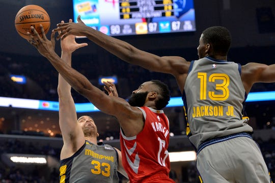 Houston Rockets guard James Harden (13) shoots against Memphis Grizzlies center Marc Gasol (33) and forward Jaren Jackson Jr. (13) in the first half on Saturday in Memphis.