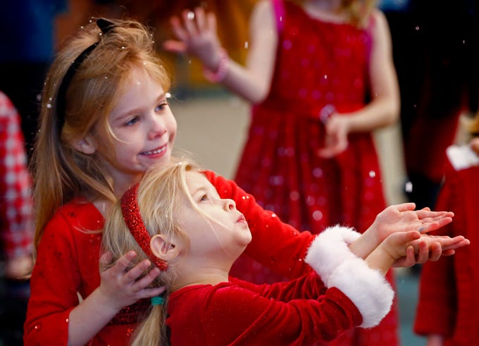 Taylor (left) and Hailey Meshberger try catching snowflakes falling in the lobby of Crosspoint Community Church before the start of the annual Jingle Jam on Dec. 15.