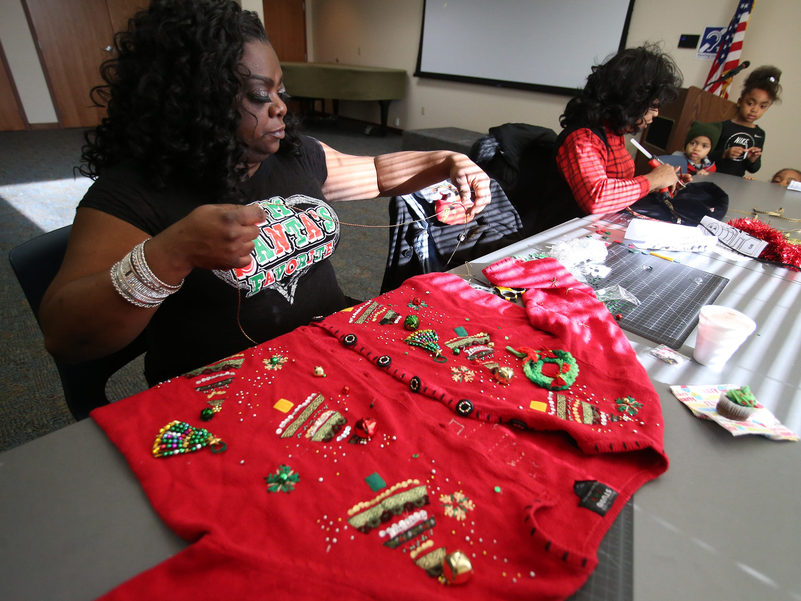 Trina Broughton adds to her creation during an Ugly Christmas Sweater workshop at the Wauwatosa Library on Dec. 15.