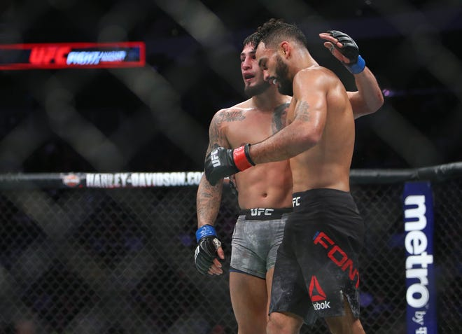 Sergio Pettis (blue gloves) and Rob Font greet each other after  Font won their bantamweight fight Saturday night during UFC Fight Night at Fiserv Forum