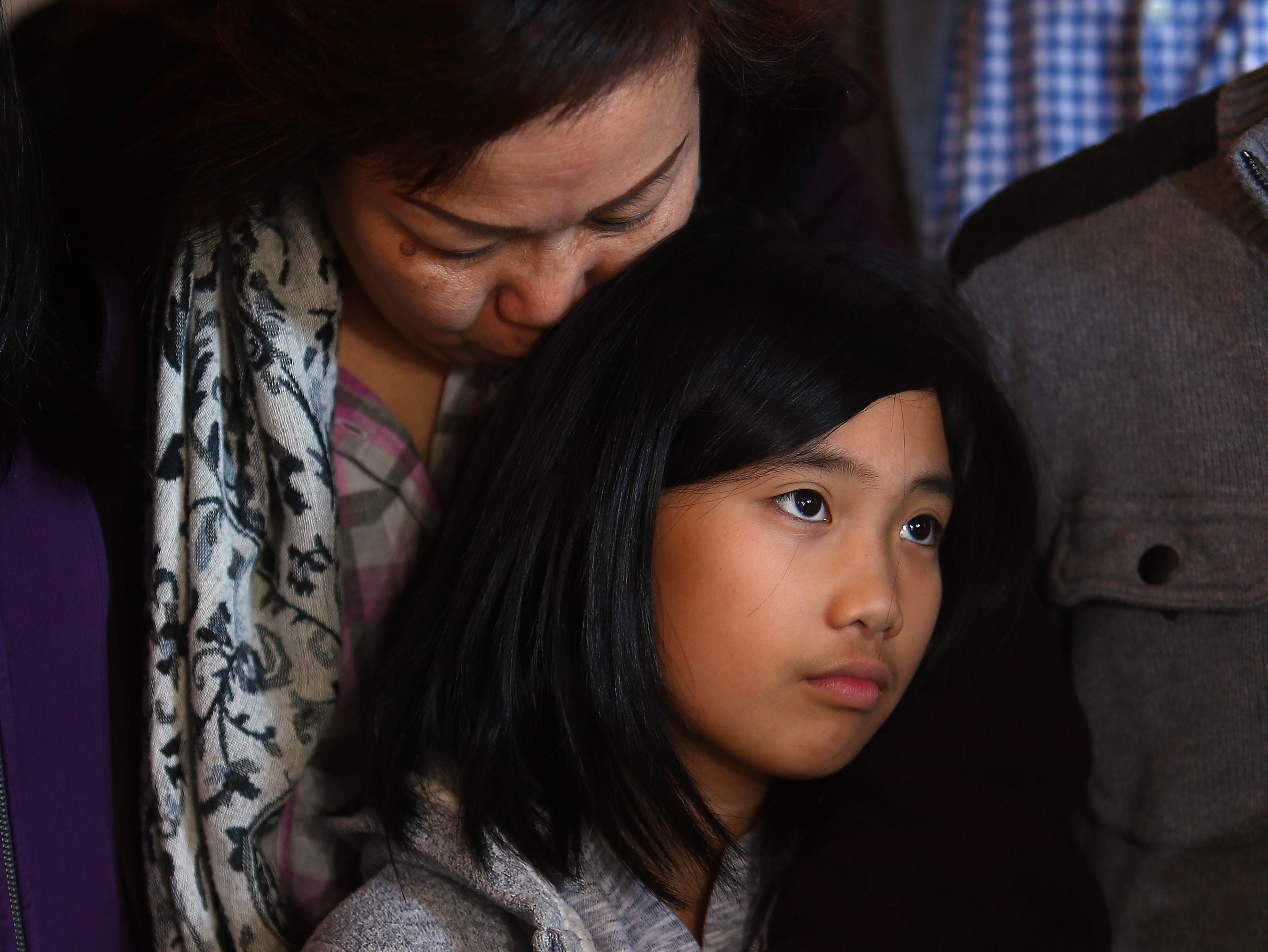 Mariana Sunarto, wife of Harry Pangemanan hugs their 11-year-old daughter during a news conference at CaiÕs Cafe in Metuchen NJ, celebrating a federal district court judge granting a temporary restraining order halting deportations of Indonesian Christian residents of Central Jersey in response to a federal class action lawsuit. February 3, 2018. Metuchen, NJ.
