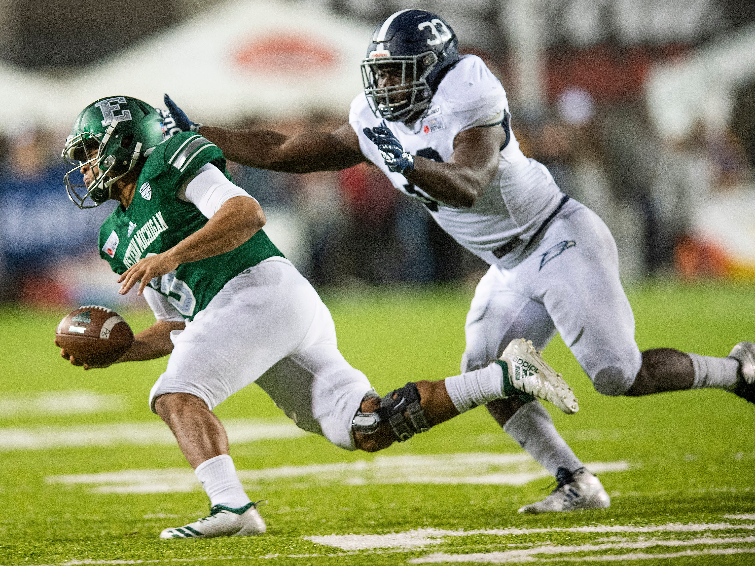 Eastern Michigan quarterback Mike Glass, III, (9)  is chased down by Georgia Southern inside linebacker Tomarcio Reese (33) in the Raycom Media  Camellia Bowl held at Cramton Bowl in Montgomery, Ala., on Saturday December 15, 2018.