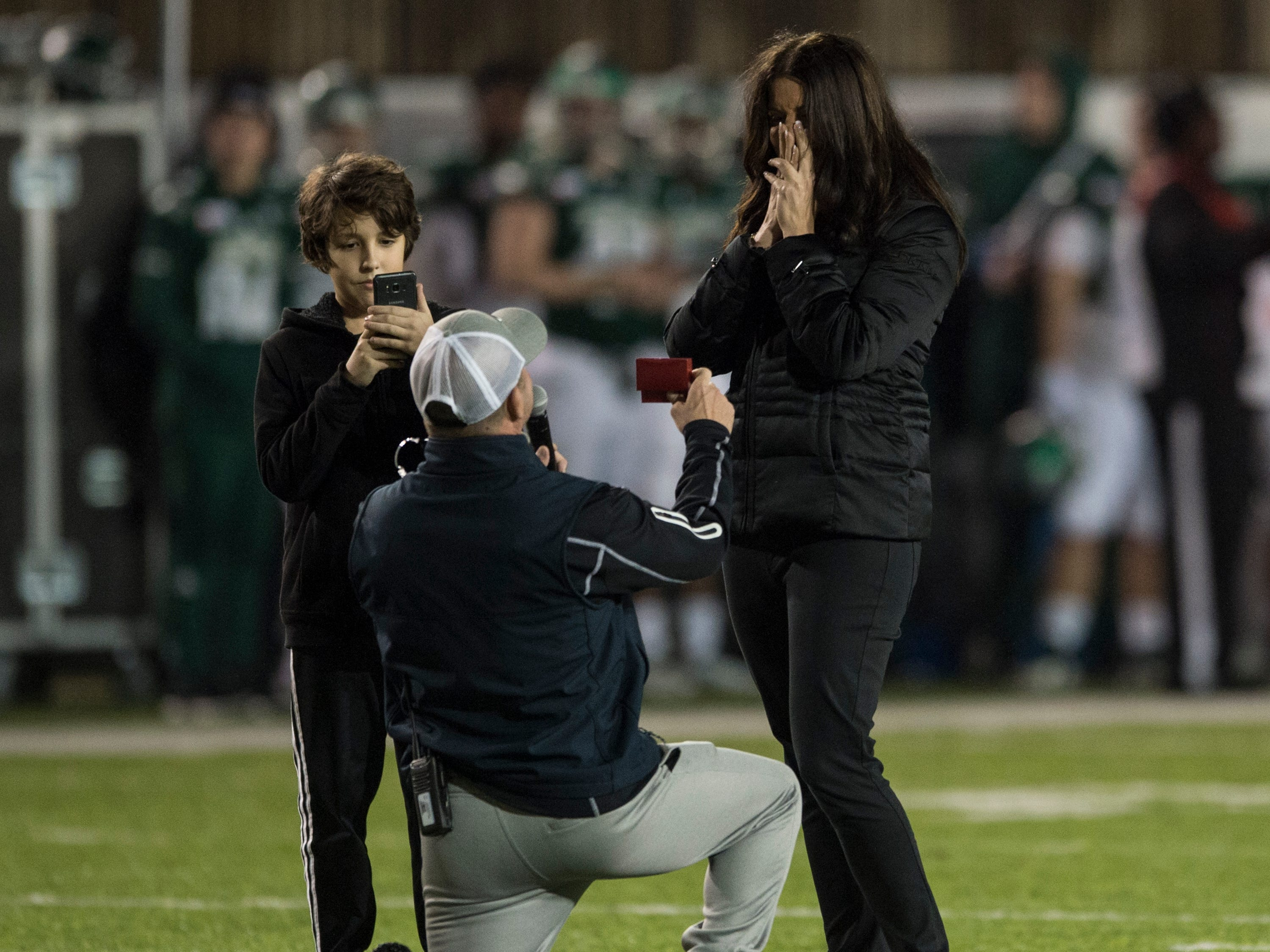 Ron Foster, director of hospitality for the Camellia Bowl, proposes to his girlfriend, Jen Wren, during the Camellia Bowl at Cramton Bowl in Montgomery, Ala., on Saturday, Dec. 15, 2018. Georgia Southern defeated Eastern Michigan 23-21.