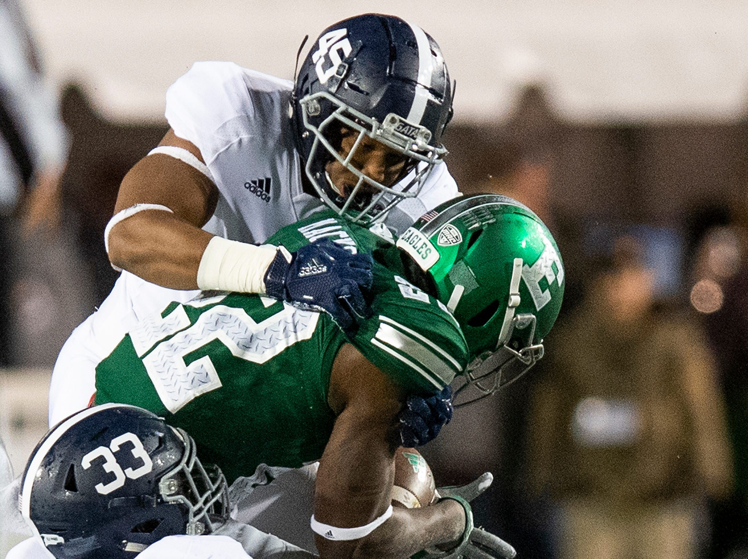 Eastern Michigan running back Karmi Mackey (22) is stopped by Georgia Southern inside linebacker Rashad  (45) and  inside linebacker Tomarcio Reese (33) in the Raycom Media  Camellia Bowl held at Cramton Bowl in Montgomery, Ala., on Saturday December 15, 2018.