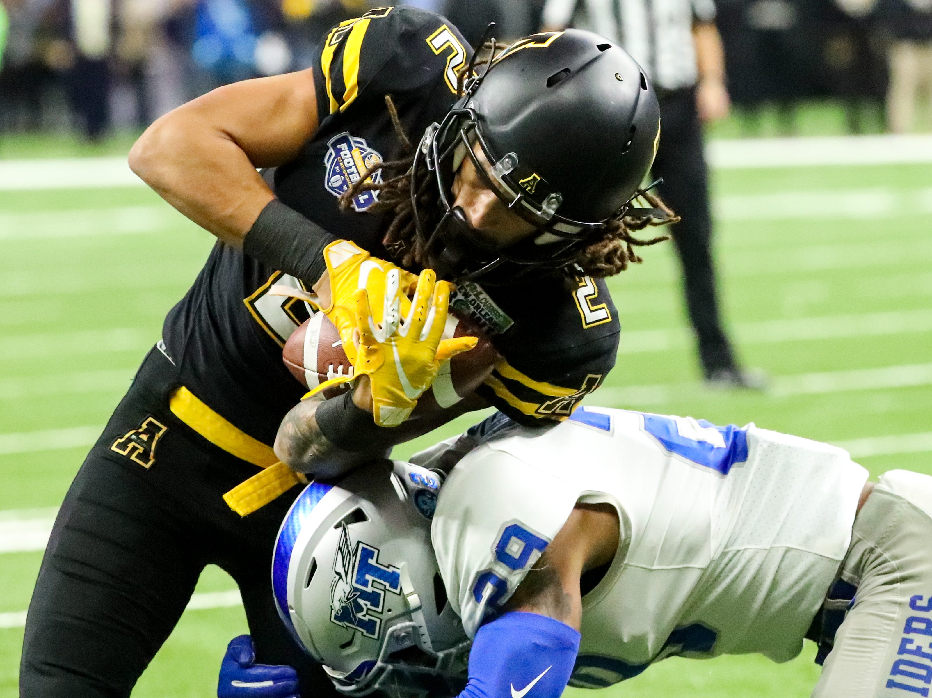 Appalachian State Mountaineers wide receiver Corey Xavier Sutton (2) is taken down by Middle Tennessee Blue Raiders cornerback Darryl Randolph (29) during the first half at the Mercedes-Benz Superdome Saturday, Dec. 15, 2018, in New Orleans, La.