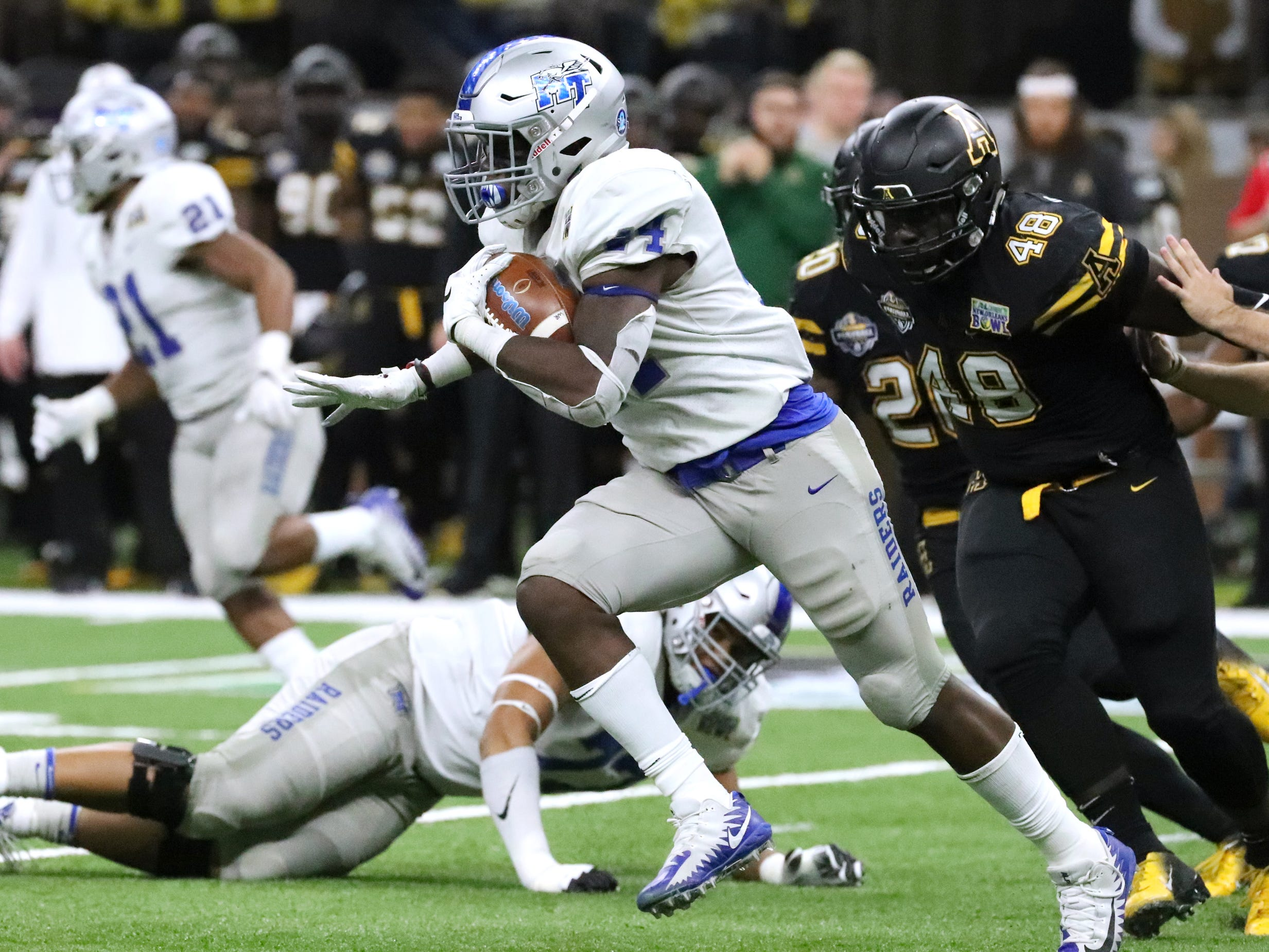 Middle Tennessee Blue Raiders running back Chaton Mobley (44) runs the ball as Appalachian State Mountaineers defensive lineman Demetrius Taylor (48) comes up from behind on Saturday, Dec. 15, 2018, during the New Orleans Bowl.