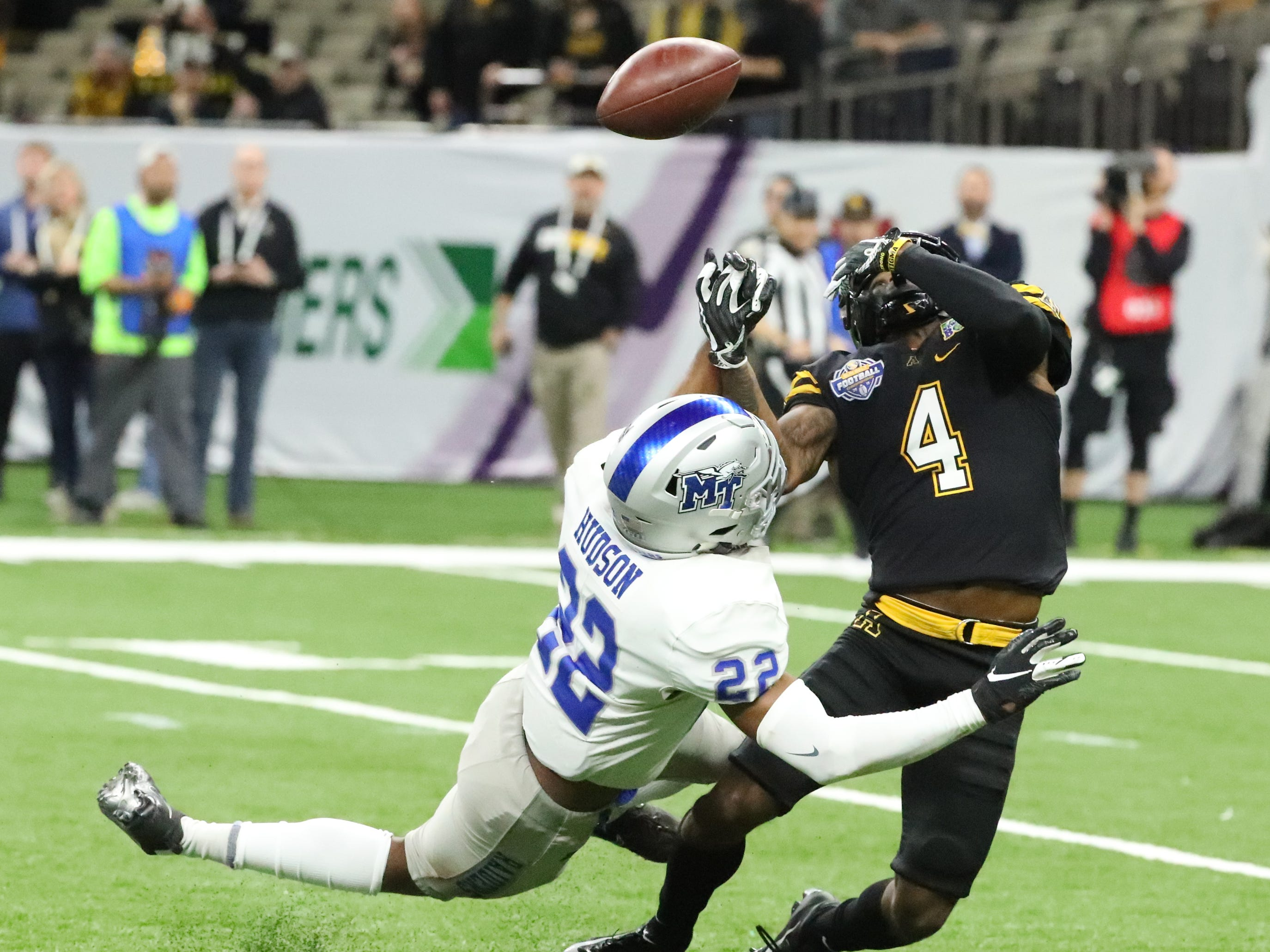 Appalachian State Mountaineers wide receiver Dominique Heath (4) attempts to catch a pass as Middle Tennessee Blue Raiders defensive back Cordell Hudson (22) covers him and Middle Tennessee Blue Raiders safety Reed Blankenship (12) moves in later to intercept the catch on Saturday, Dec. 15, 2018, during the New Orleans Bowl.