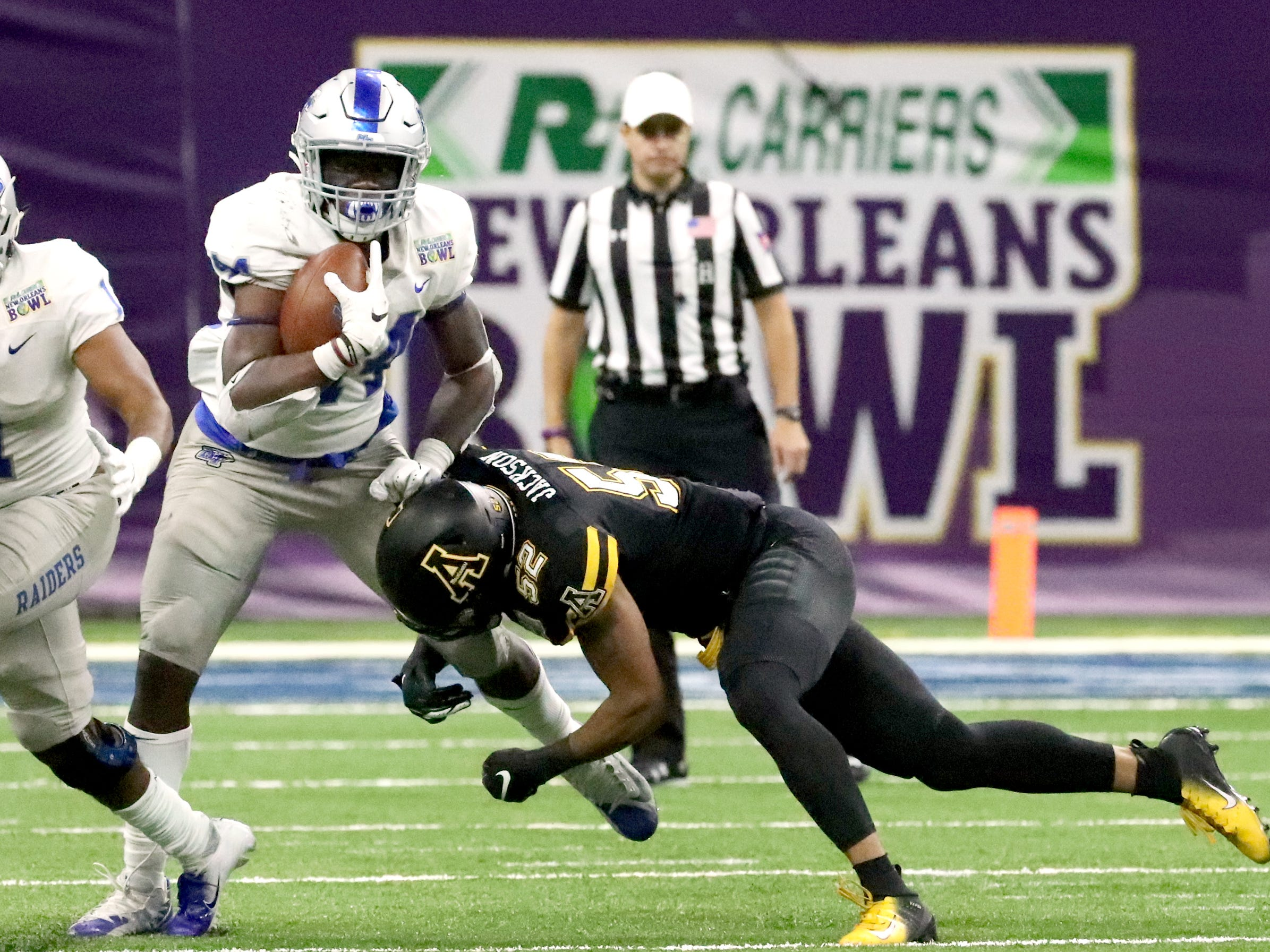 Middle Tennessee Blue Raiders running back Chaton Mobley (44) runs the ball as Appalachian State Mountaineers linebacker D'Marco Jackson (52) tackles him on Saturday, Dec. 15, 2018, during the New Orleans Bowl.