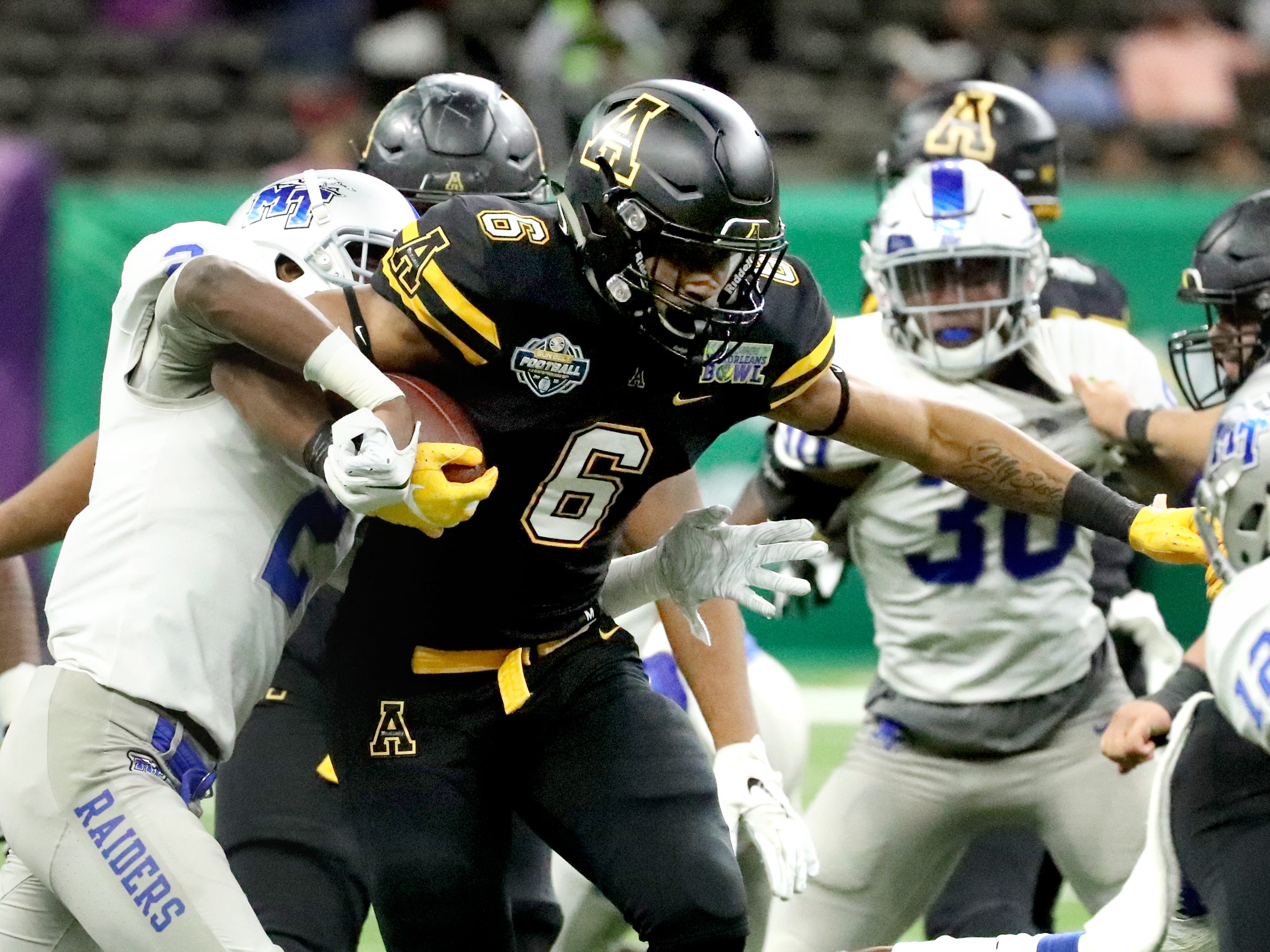 Appalachian State Mountaineers running back Camerun Peoples (6) runs the ball as Middle Tennessee Blue Raiders defensive back Chris Stamps (2) tackles him on Saturday, Dec. 15, 2018, during the New Orleans Bowl.