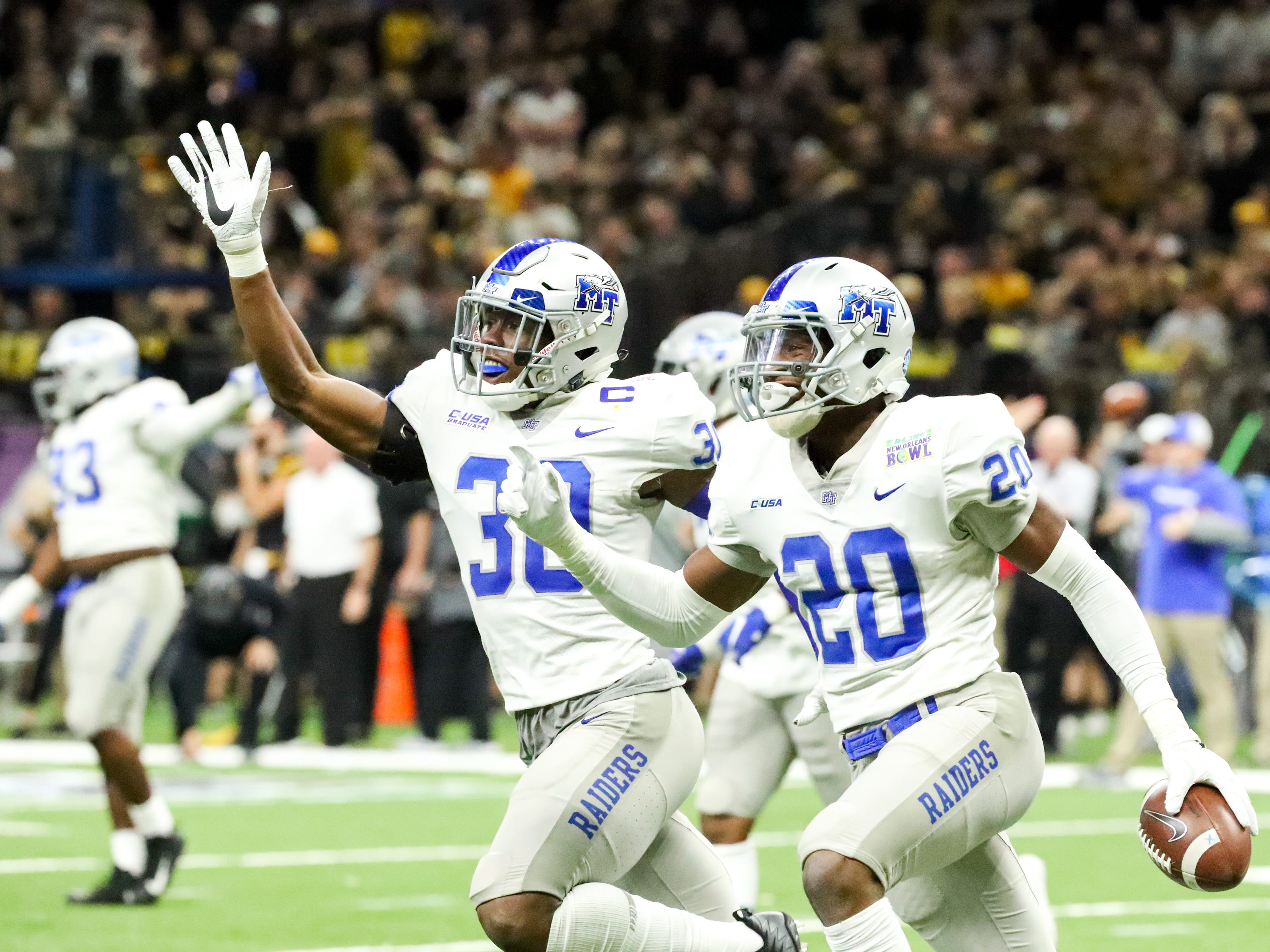 Middle Tennessee Blue Raiders linebacker DQ Thomas (20) and Middle Tennessee Blue Raiders linebacker Darius Harris (30) celebrate Thomas' fumble recovery from the Appalachian State Mountaineers during the first half at the Mercedes-Benz Superdome Saturday, Dec. 15, 2018, in New Orleans, La.