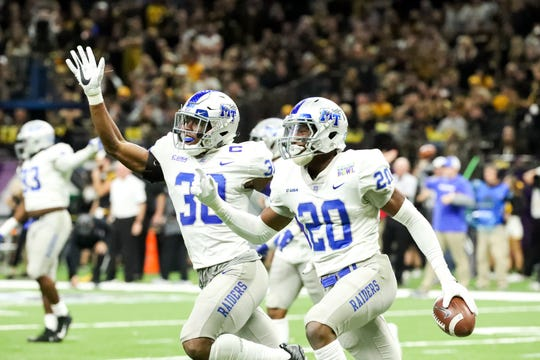 MTSU linebackers DQ Thomas (20) and Darius Harris (30) celebrate Thomas' fumble recovery during the New Orleans Bowl on Dec. 15, 2018.