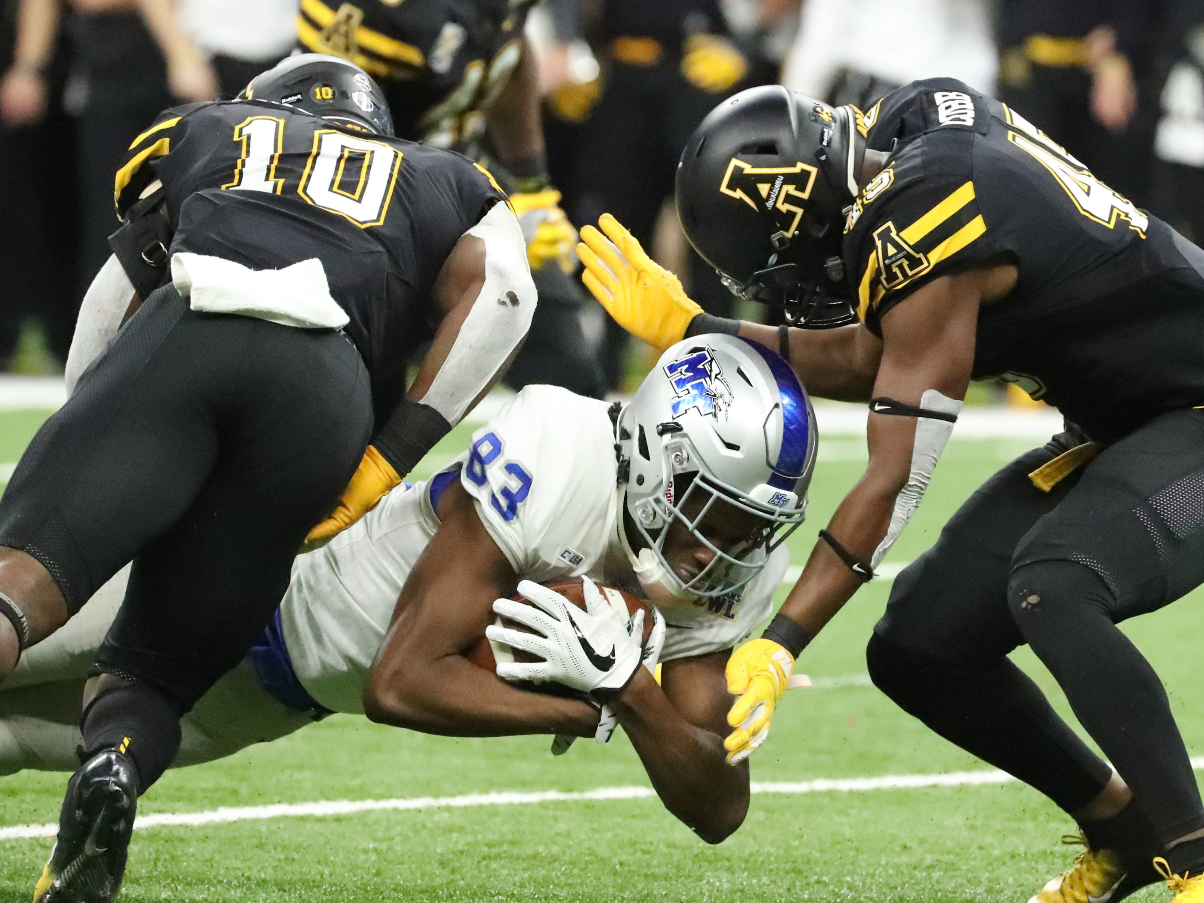 Middle Tennessee Blue Raiders wide receiver Jimmy Marshall (83) dives for yardage as Appalachian State Mountaineers linebacker Tim Frizzell (10) and Appalachian State Mountaineers linebacker Trey Cobb (45) move in for the tackle on Saturday, Dec. 15, 2018, during the New Orleans Bowl.