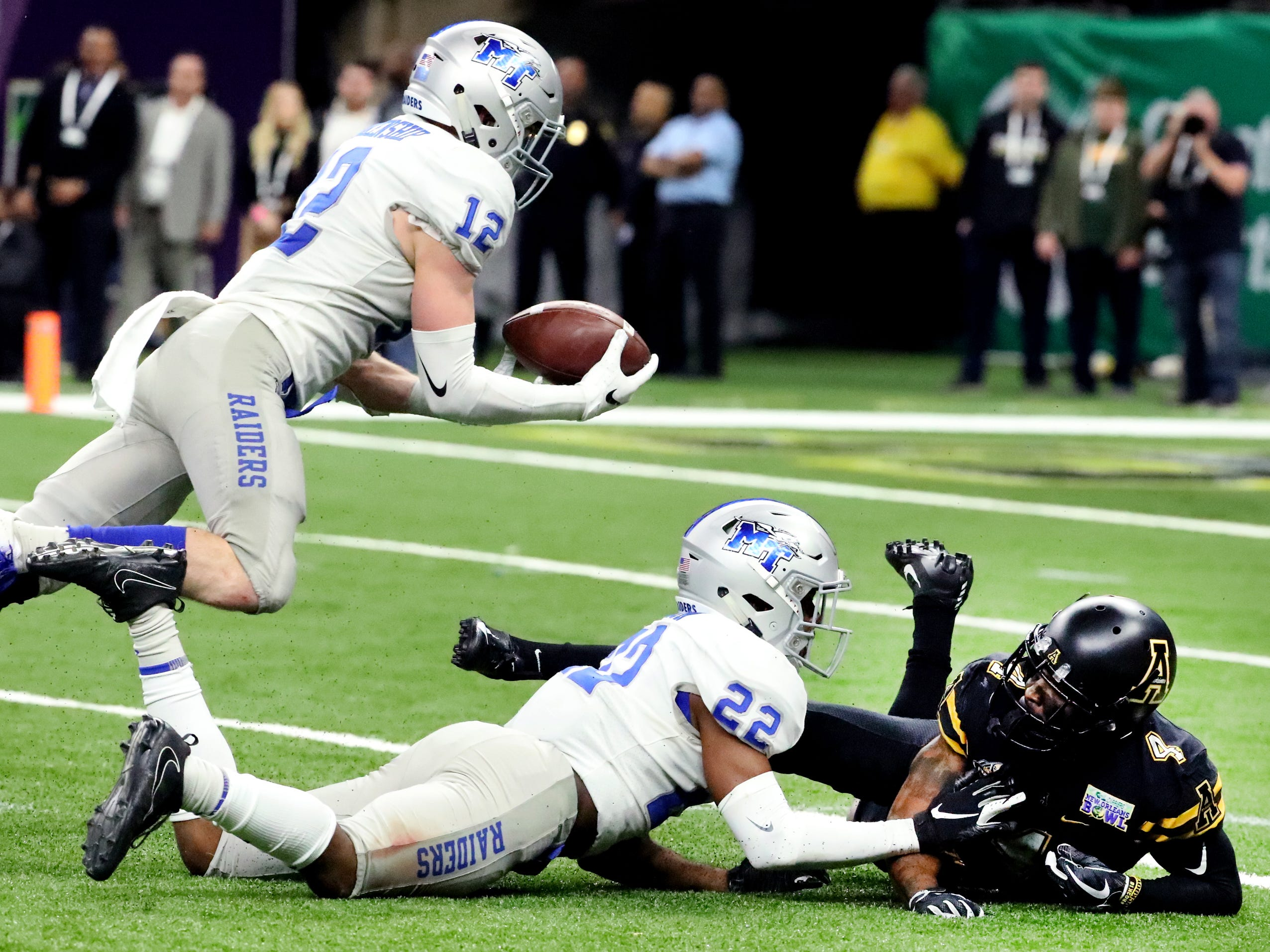 Middle Tennessee Blue Raiders safety Reed Blankenship (12) intercepts a pass intended for Appalachian State Mountaineers wide receiver Dominique Heath (4) as Middle Tennessee Blue Raiders defensive back Cordell Hudson (22) covers him on Saturday, Dec. 15, 2018, during the New Orleans Bowl.