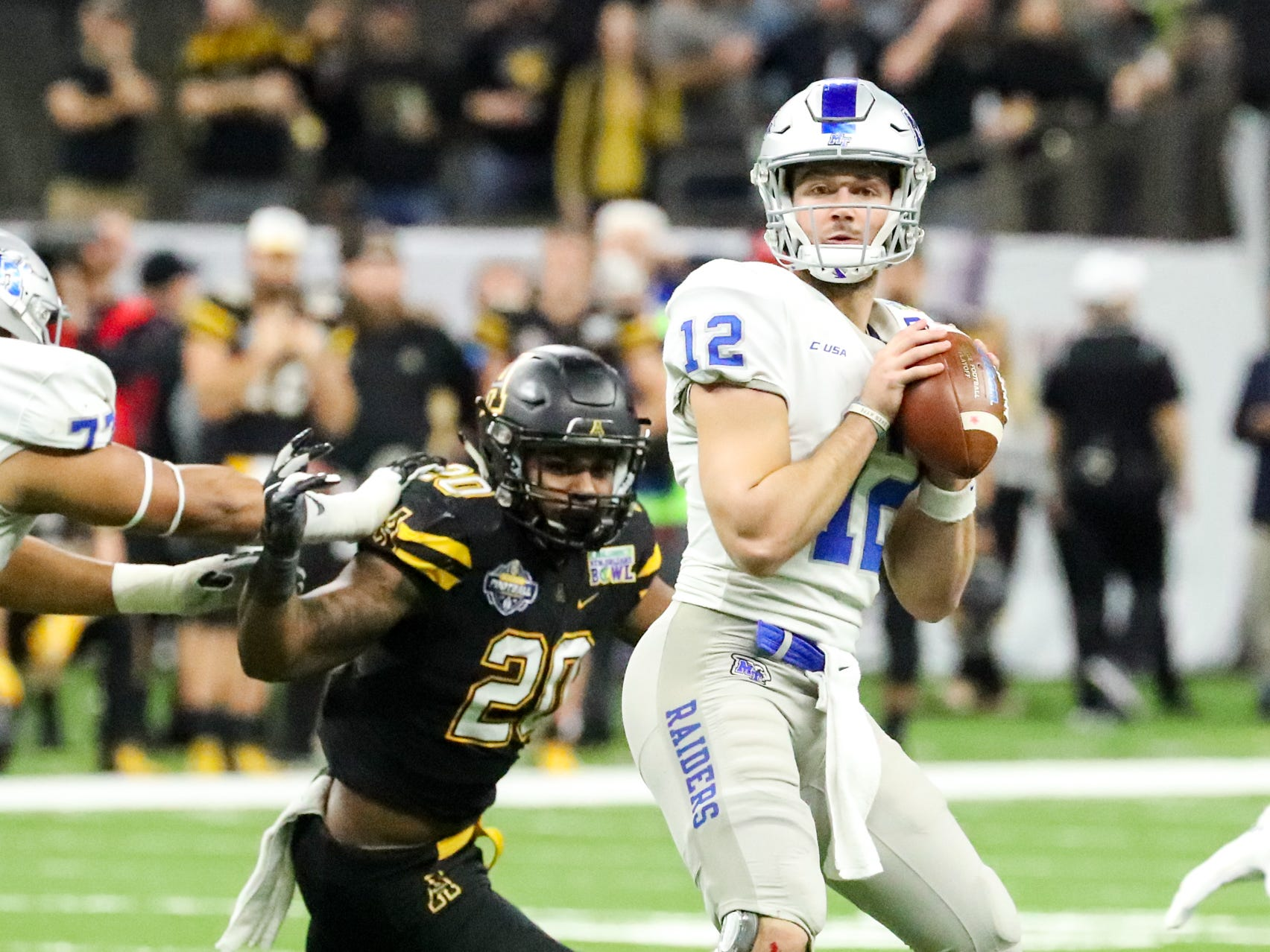 Middle Tennessee Blue Raiders quarterback Brent Stockstill (12) looks for an open receiver as Appalachian State Mountaineers linebacker Noel Cook (20) puts pressure on him during the first half at the Mercedes-Benz Superdome Saturday, Dec. 15, 2018, in New Orleans, La.