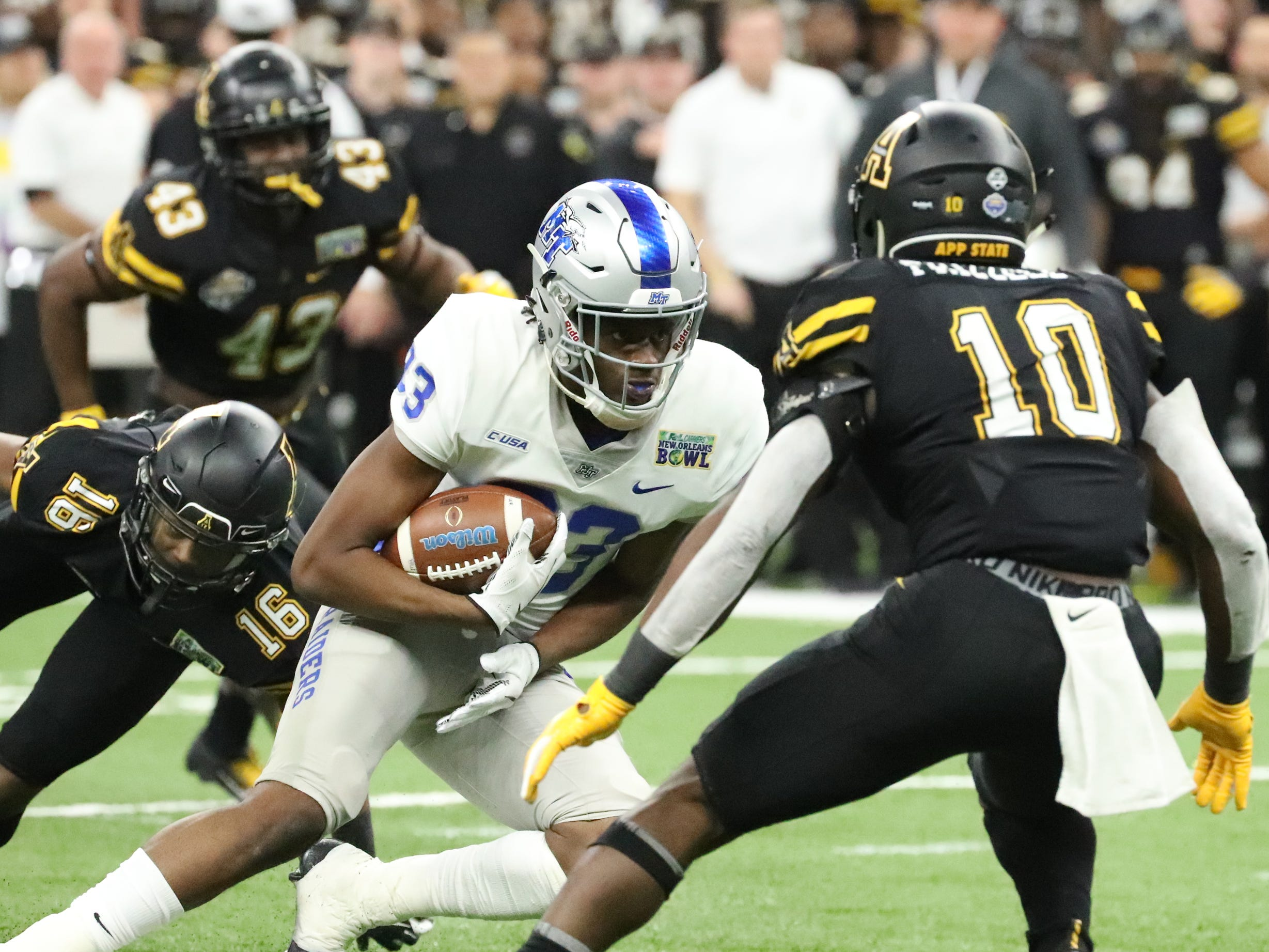 Middle Tennessee Blue Raiders defensive back Wesley Bush (23) runs the ball as Appalachian State Mountaineers linebacker Tim Frizzell (10) moves in for a tackle and Appalachian State Mountaineers defensive back Shaun Jolly (16) misses the tackle on Saturday, Dec. 15, 2018, during the New Orleans Bowl.