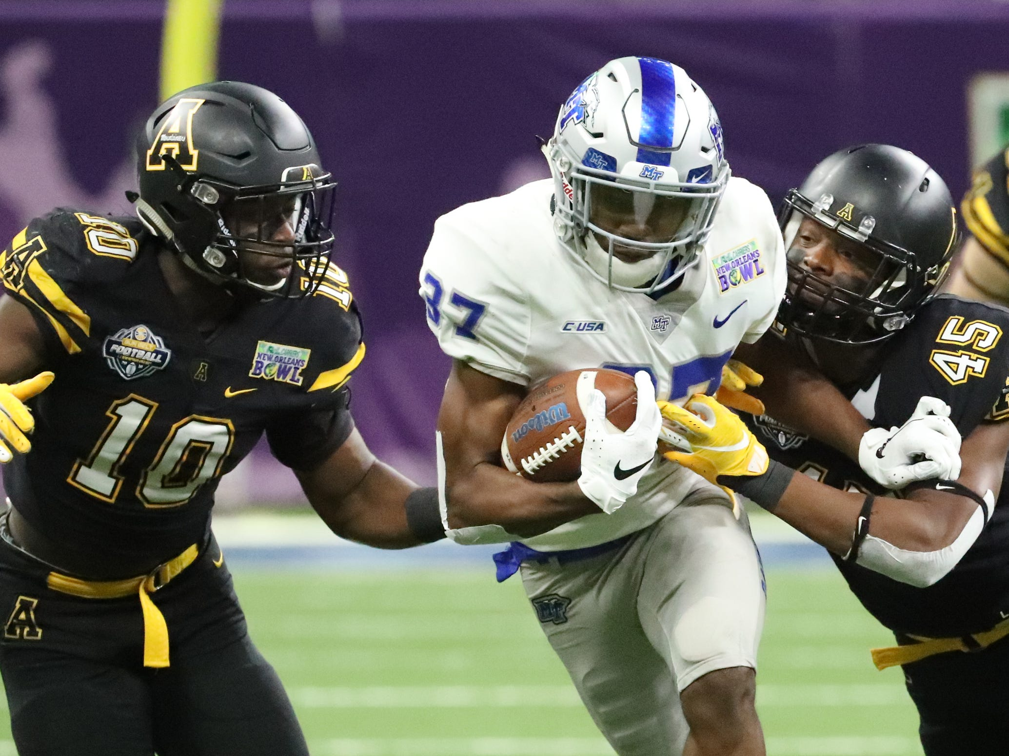 Middle Tennessee Blue Raiders wide receiver Patrick Smith (37) runs the ball as Appalachian State Mountaineers linebacker Tim Frizzell (10) and Appalachian State Mountaineers linebacker Trey Cobb (45) move for the tackle on Saturday, Dec. 15, 2018, during the New Orleans Bowl.