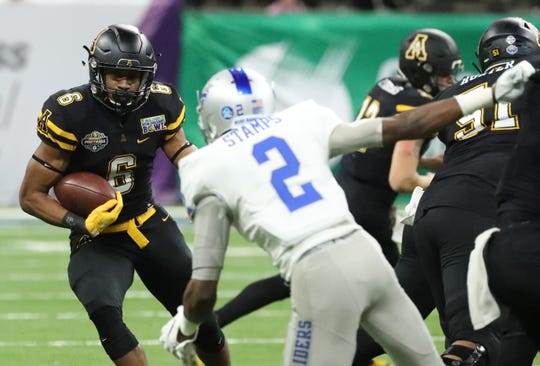 Appalachian State Mountaineers running back Camerun Peoples (6) runs the ball as Middle Tennessee Blue Raiders defensive back Chris Stamps (2) moves in for a tackle on Saturday, Dec. 15, 2018, during the New Orleans Bowl.