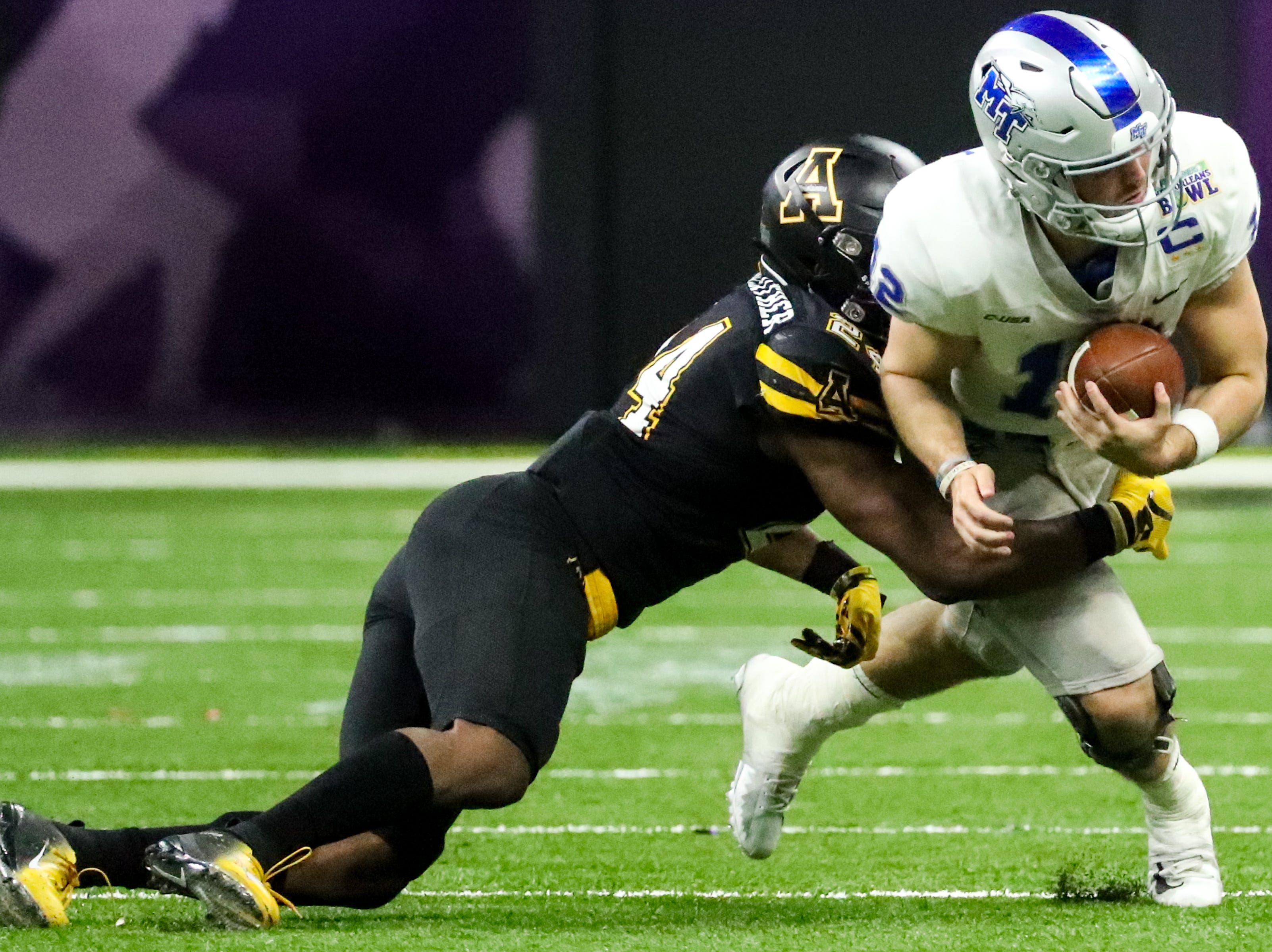 Middle Tennessee Blue Raiders quarterback Brent Stockstill (12) is tackled by Appalachian State Mountaineers linebacker Akeem Davis-Gaither (24) during the first half at the Mercedes-Benz Superdome Saturday, Dec. 15, 2018, in New Orleans, La.