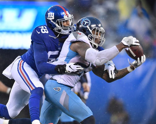 Titans running back Derrick Henry (22) pulls in a catch in the fourth quarter defended by Giants linebacker Tae Davis (58) at MetLife Stadium Sunday, Dec. 16, 2018, in East Rutherford, N.J.