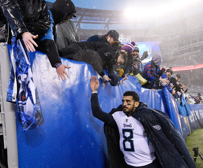 Titans quarterback Marcus Mariota slaps hands with fans after the team's win over the Giants on Sunday.