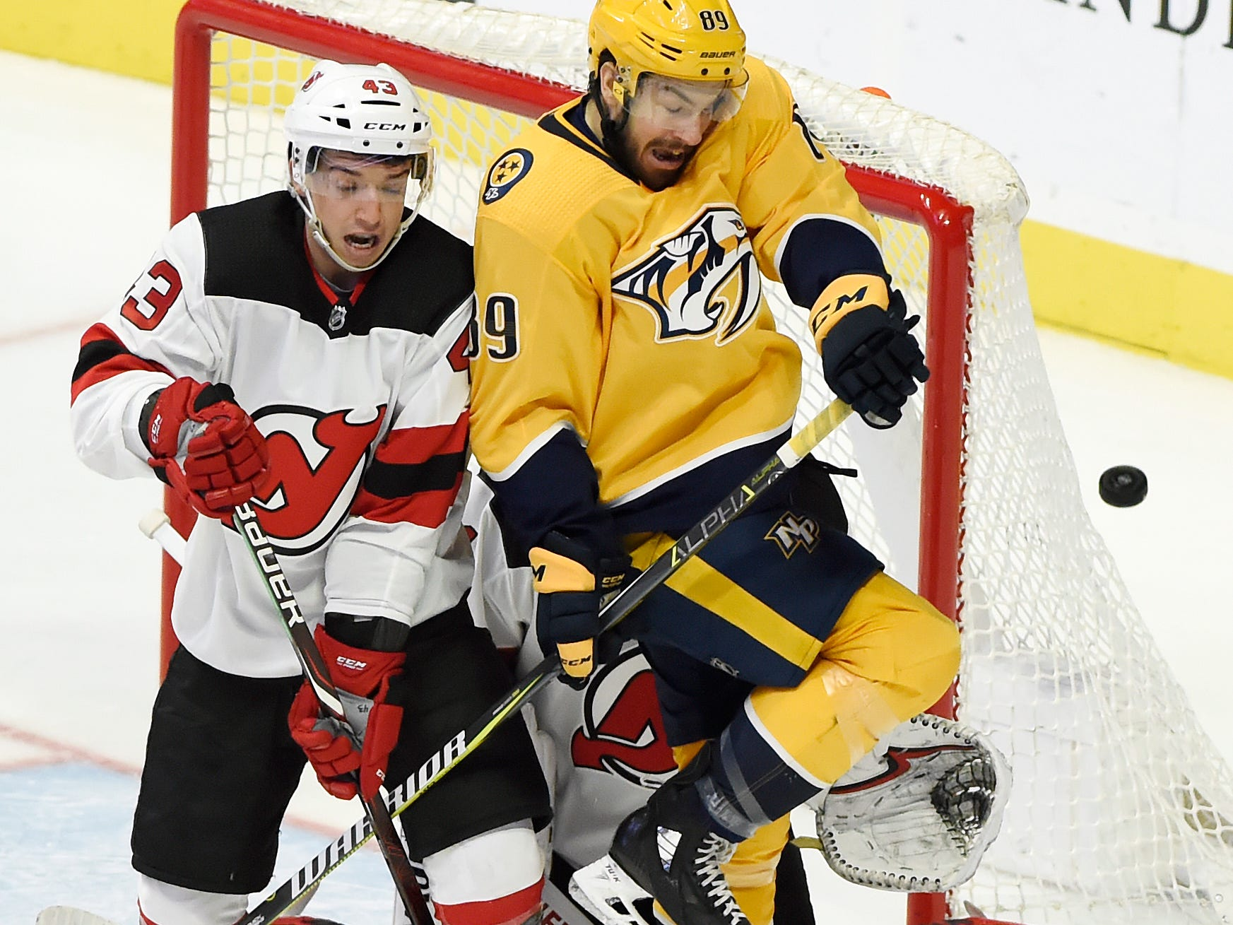 New Jersey Devils left wing Brett Seney (43) and Nashville Predators center Frederick Gaudreau (89) try to move out of the way of a shot during the third of an NHL hockey game Saturday, Dec. 15, 2018, in Nashville, Tenn. The Predators won 2-1 in an shootout.