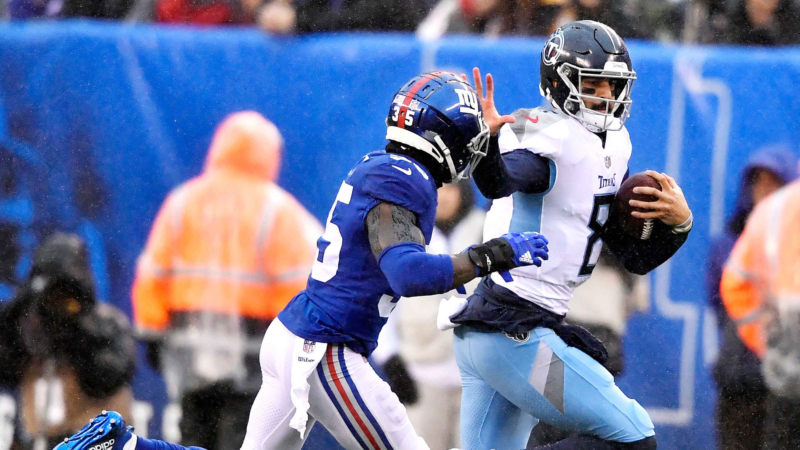 Titans quarterback Marcus Mariota (8) rushes for a first down in the first quarter defended by Giants cornerback Curtis Riley (35) at MetLife Stadium Sunday, Dec. 16, 2018, in East Rutherford, N.J.