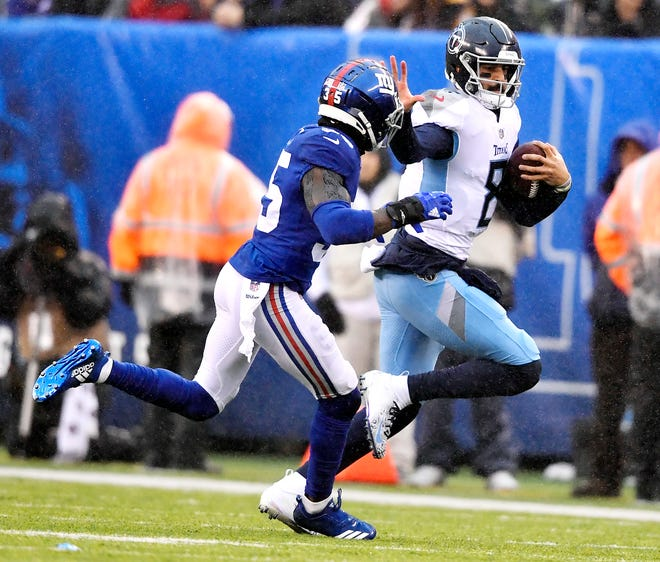 Titans quarterback Marcus Mariota (8) rushes for a first down in the first quarter Sunday while being pursued by Giants cornerback Curtis Riley (35).