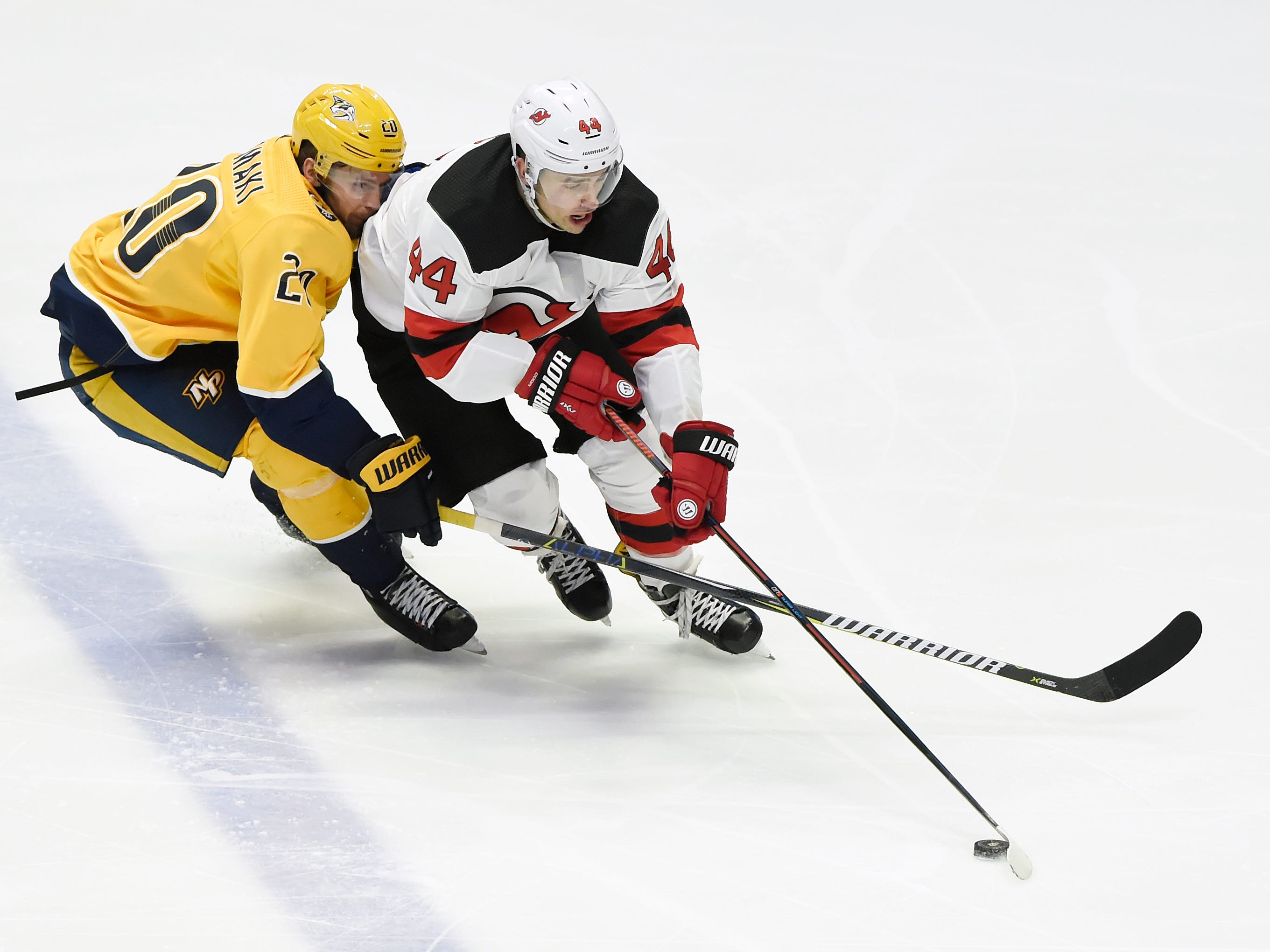 New Jersey Devils left wing Miles Wood (44) maneuvers the puck past Nashville Predators right wing Miikka Salomaki (20), during the second period of an NHL hockey game Saturday, Dec. 15, 2018, in Nashville, Tenn.