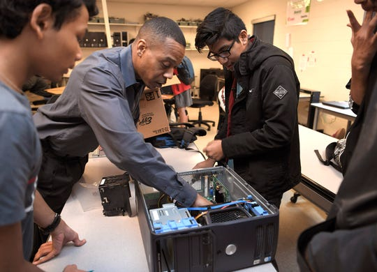 Industry certification courses in Metro Nashville Public Schools don't always earn students college credit, but they teach valuable job skills. In this file photo, Overton High School teacher Sam Banks helps students put a computer back together during Computer Networking class on Dec. 13, 2018.