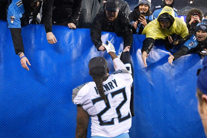 Titans running back Derrick Henry (22) signs autographs for fans after the team's 17-0 win over the Giants on Sunday.
