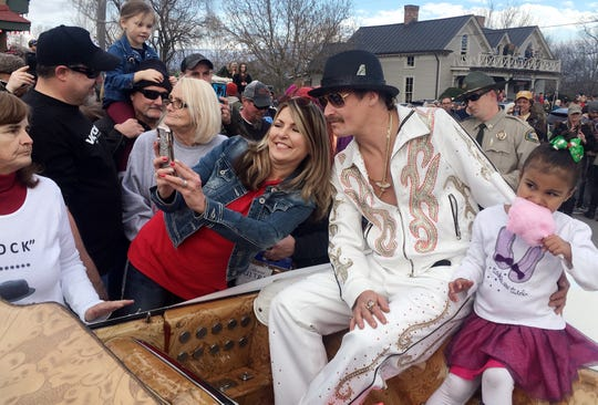 People take selfies with Kid Rock as he  rides in the Leiper's Fork Christmas Parade on Saturday, Dec. 15, 2018.