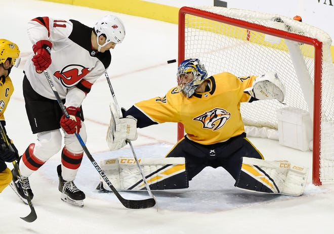 Predators goaltender Juuse Saros deflects a shot by New Jersey Devils center Brian Boyle  on Saturday. Saros made 33 saves and stopped five shootout attempts as Nashville won, 2-1.